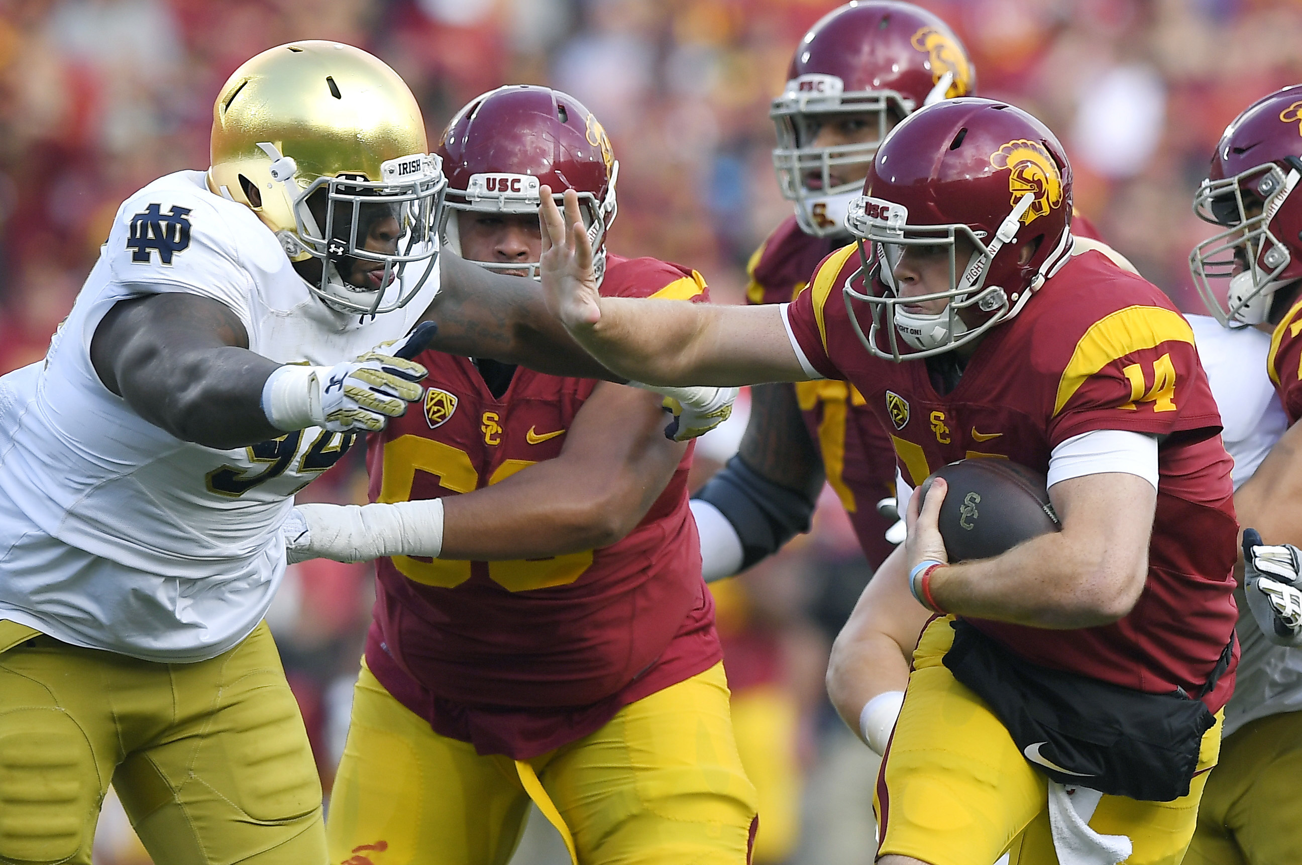 Southern California quarterback Sam Darnold, right, fends off Notre Dame defensive lineman Jarron Jones as he runs the ball during the first half of an NCAA college football game, Saturday, Nov. 26, 2016, in Los Angeles. (AP Photo/Mark J. Terrill)
