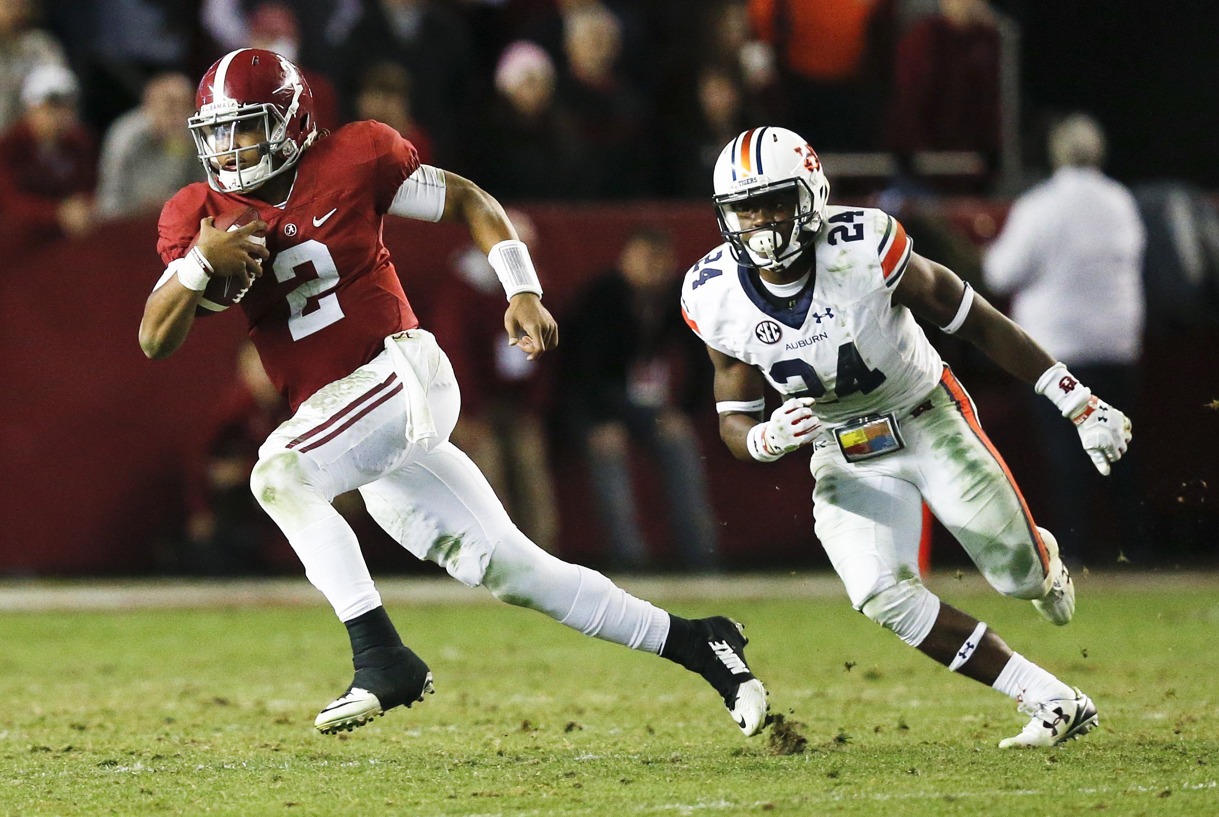 Alabama quarterback Jalen Hurts runs the ball against Auburn defensive back Daniel Thomas during the second half of the Iron Bowl NCAA college football game, Saturday, Nov. 26, 2016, in Tuscaloosa, Ala. Alabama won 30-12. (AP Photo/Brynn Anderson)