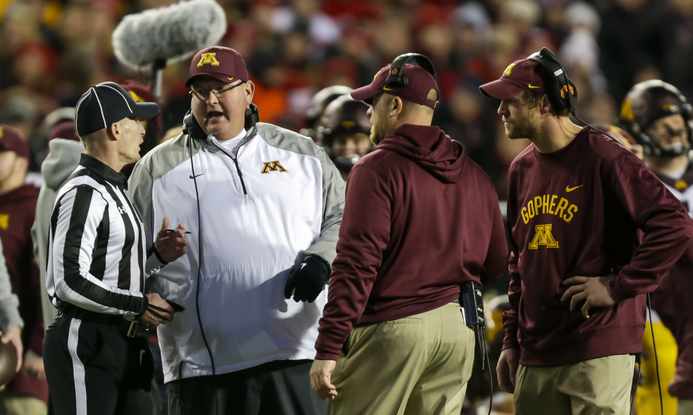 Minnesota coach Tracy Claeys, second from left, talks with an official during the second half of an NCAA college football game against Wisconsin, Saturday, Nov. 26, 2016, in Madison, Wis. Wisconsin won 31-17. (AP Photo/Andy Manis)
