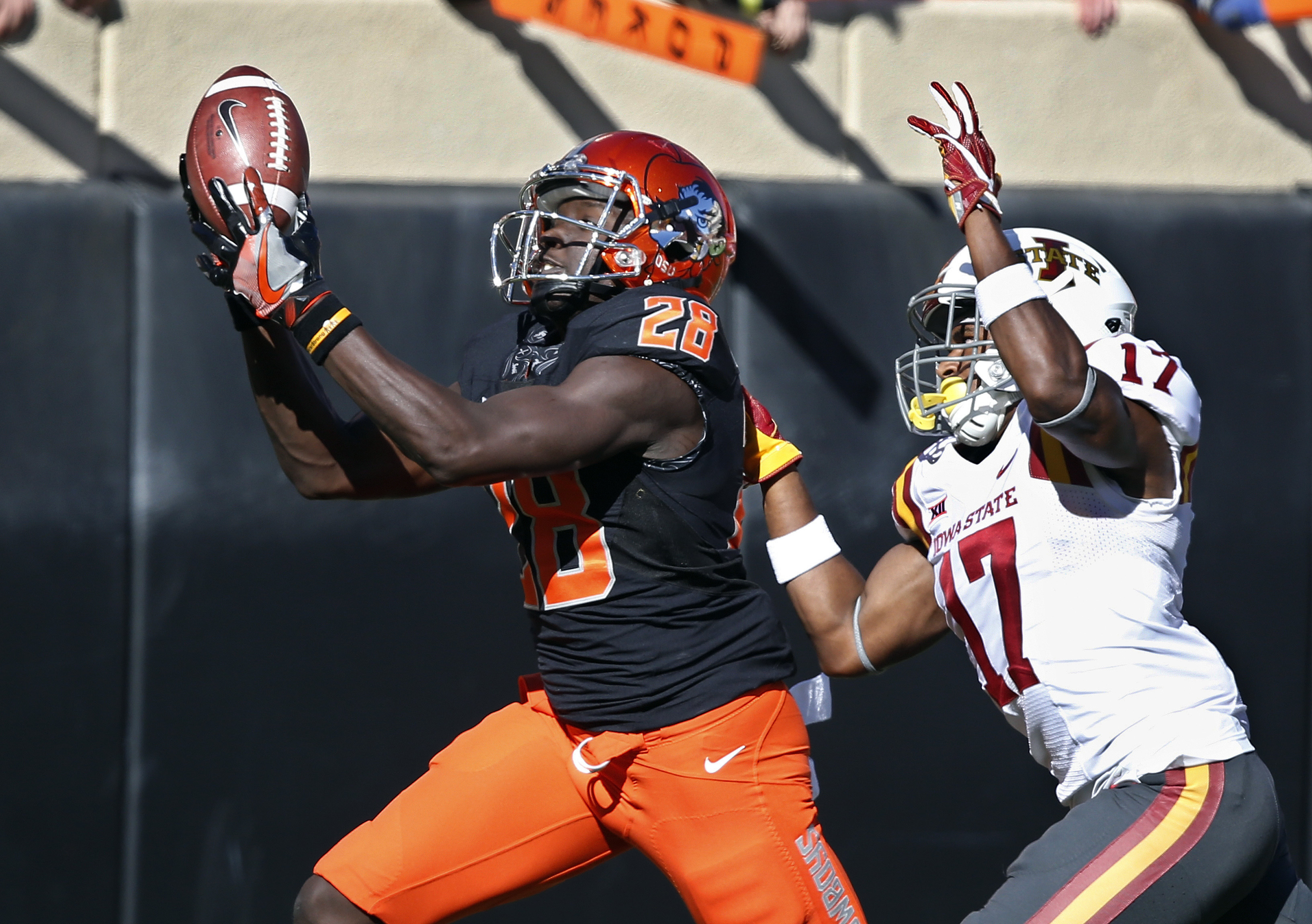 FILE - In this Oct. 8, 2016, file photo, Oklahoma State wide receiver James Washington (28) catches a pass in front of Iowa State defensive back Jomal Wiltz (17) in the second quarter of an NCAA college football game in Stillwater, Okla. For the second st