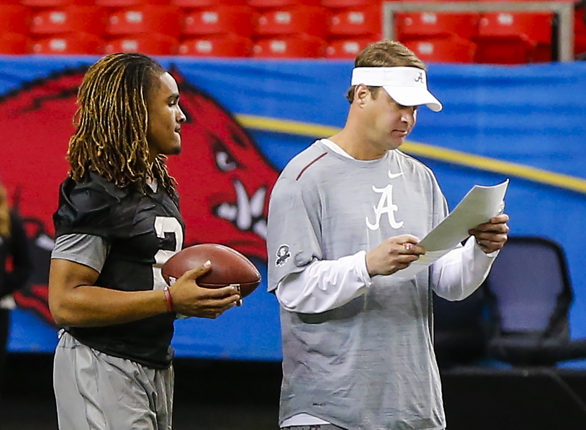 Alabama offensive coordinator Lane Kiffin, right, talks with quarterback Jalen Hurts (2) during practice for the Southeastern Conference Championship NCAA college football game where they will play Florida, Friday, Dec. 2, 2016, in Atlanta. (AP Photo/Butc