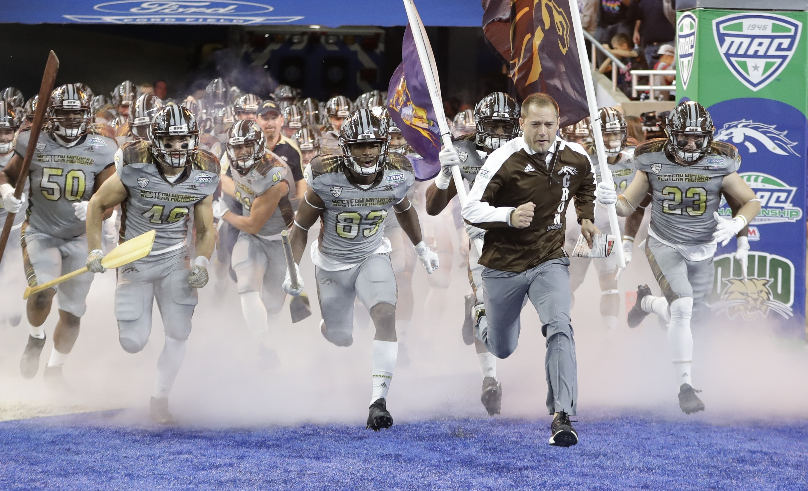 Western Michigan head coach P.J. Fleck runs onto the field with his team before the Mid-American Conference championship NCAA college football game against Ohio, Friday, Dec. 2, 2016, in Detroit. (AP Photo/Carlos Osorio)