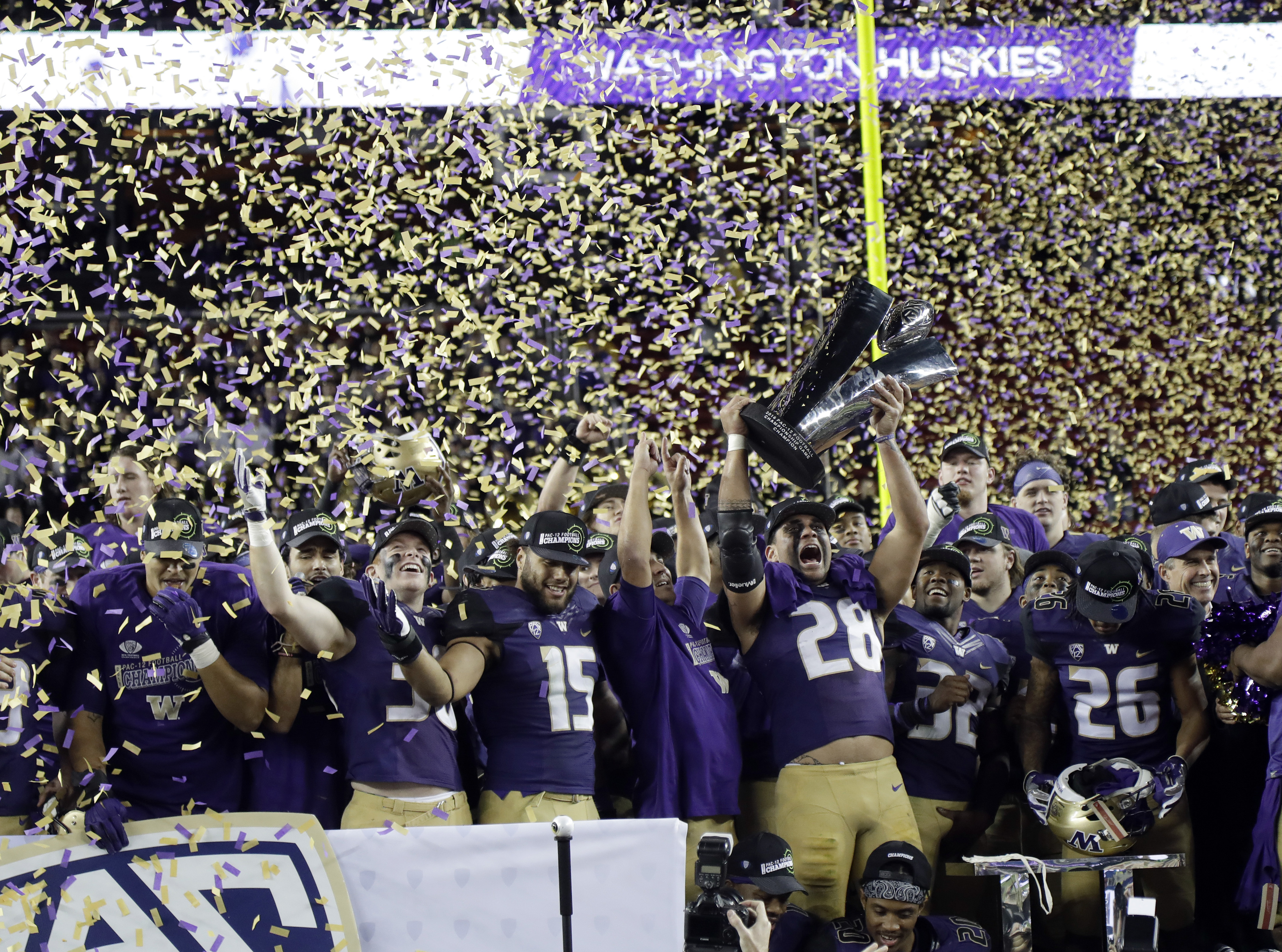 Washington players celebrate with the trophy after a 41-10 win over Colorado in the Pac-12 Conference championship NCAA college football game Friday, Dec. 2, 2016, in Santa Clara, Calif. (AP Photo/Marcio Jose Sanchez)