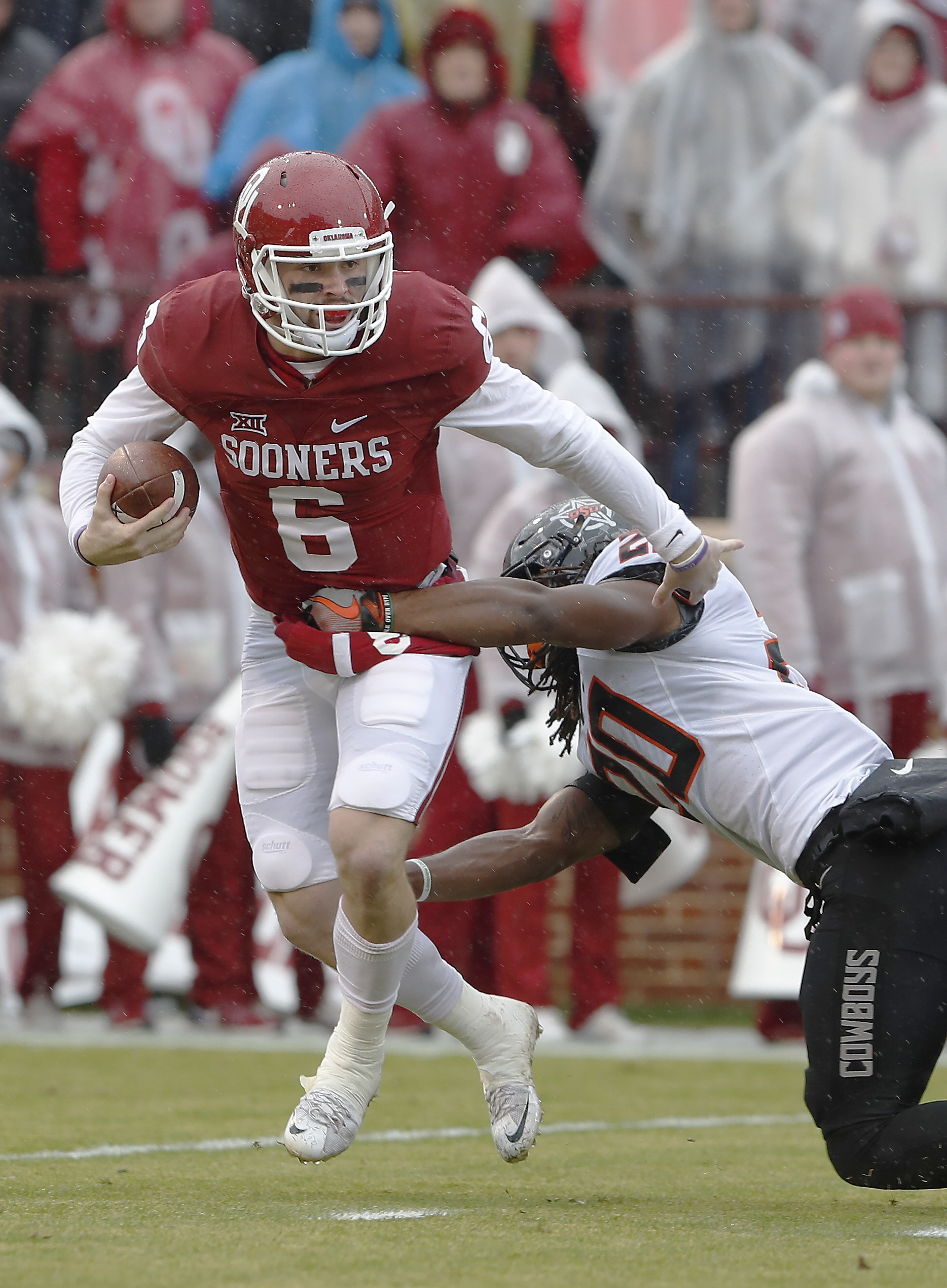 Oklahoma quarterback Baker Mayfield (6) is sacked by Oklahoma State linebacker Jordan Burton (20) during the first half of an NCAA college football game, Saturday, Dec. 3, 2016, in Norman, Okla. (AP Photo/Alonzo Adams)