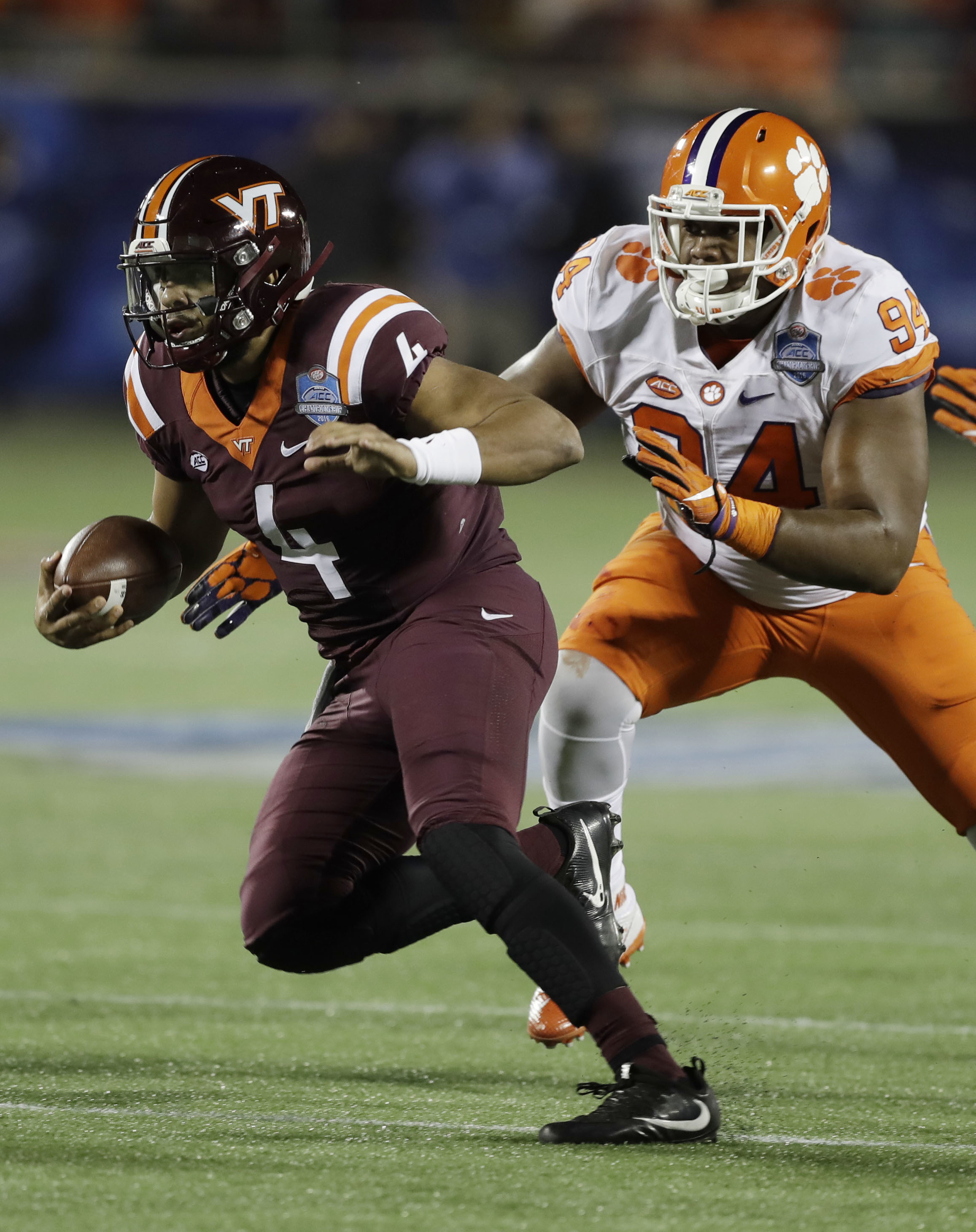Virginia Tech quarterback Jerod Evans (4) runs the ball ahead of Clemson defensive tackle Carlos Watkins (94), during the first half of the Atlantic Coast Conference championship NCAA college football game, Saturday, Dec. 3, 2016, in Orlando, Fla. (AP Pho