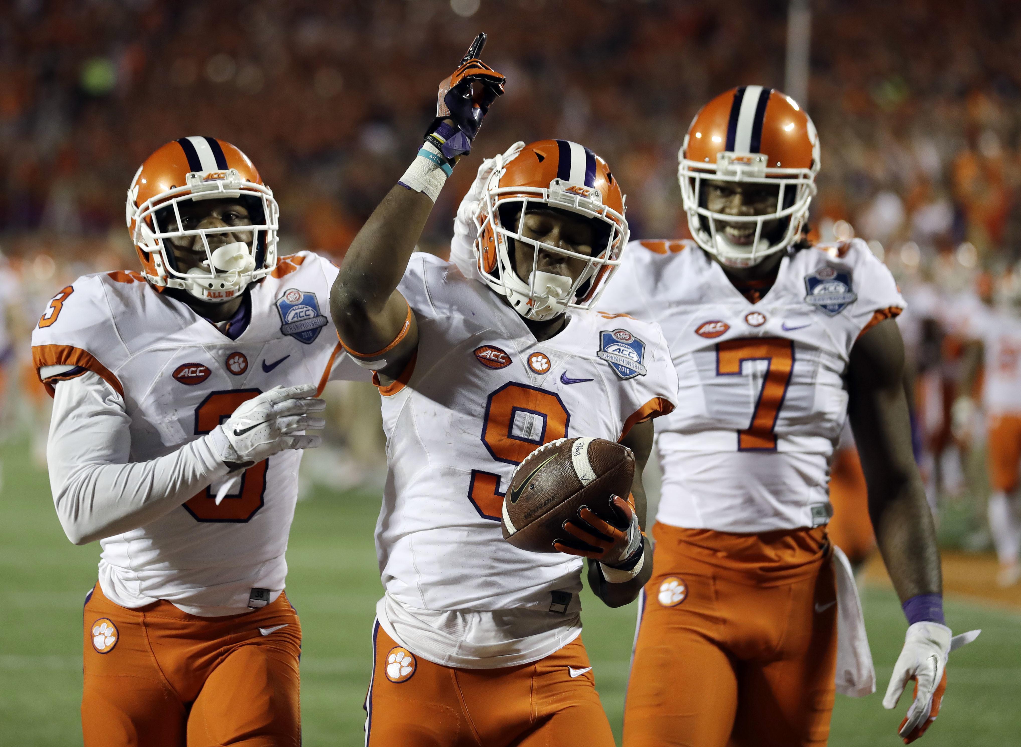 Clemson wide receivers Artavis Scott (3) and Mike Williams (7), congratulate running back Wayne Gallman (9) after Gallman scored a touchdown during the second half of the Atlantic Coast Conference championship NCAA college football game against Virginia T
