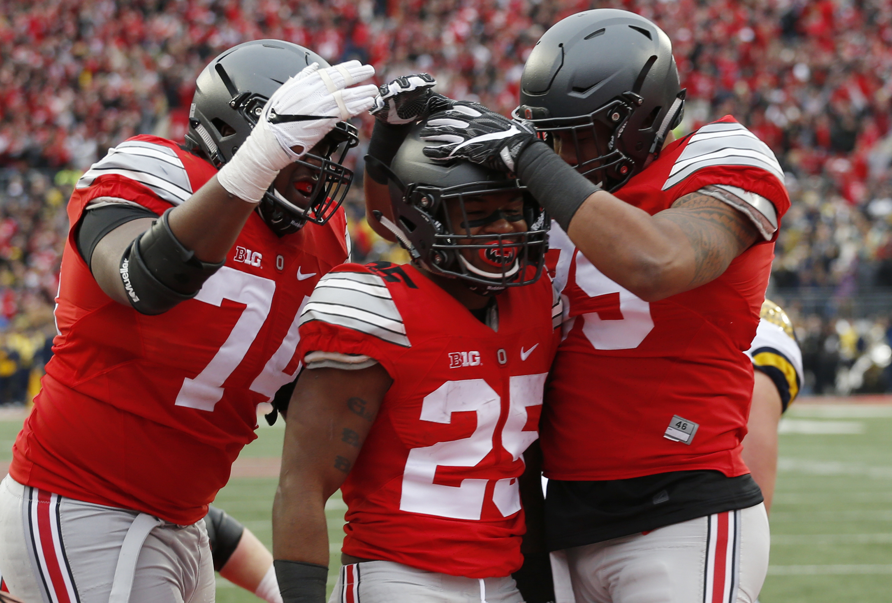 FILE - In this Nov. 26, 2016, file photo, Ohio State running back Mike Weber, center, celebrates his touchdown against Michigan with teammates Jamarco Jones, left, and Luke Farrell during the second half of an NCAA college football game in Columbus, Ohio.