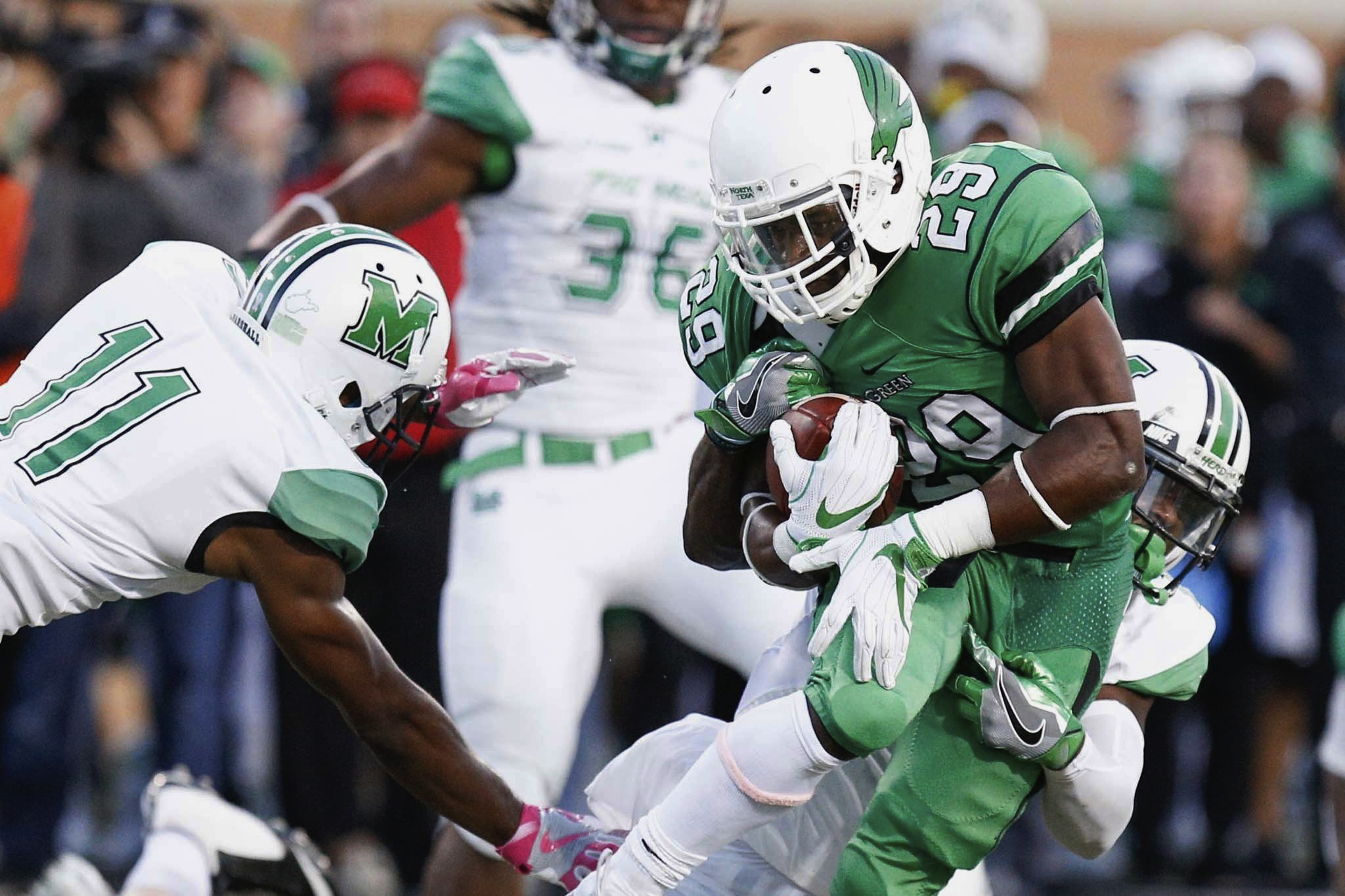 FILE- In this Oct. 8, 2016, file photo, North Texas running back Willy Ivery (29) rushes the ball, while Marshall safety C.J. Reavis (1) wraps him from behind in an NCAA college football game in Denton, Texas. North Texas will play in the Heart of Dallas