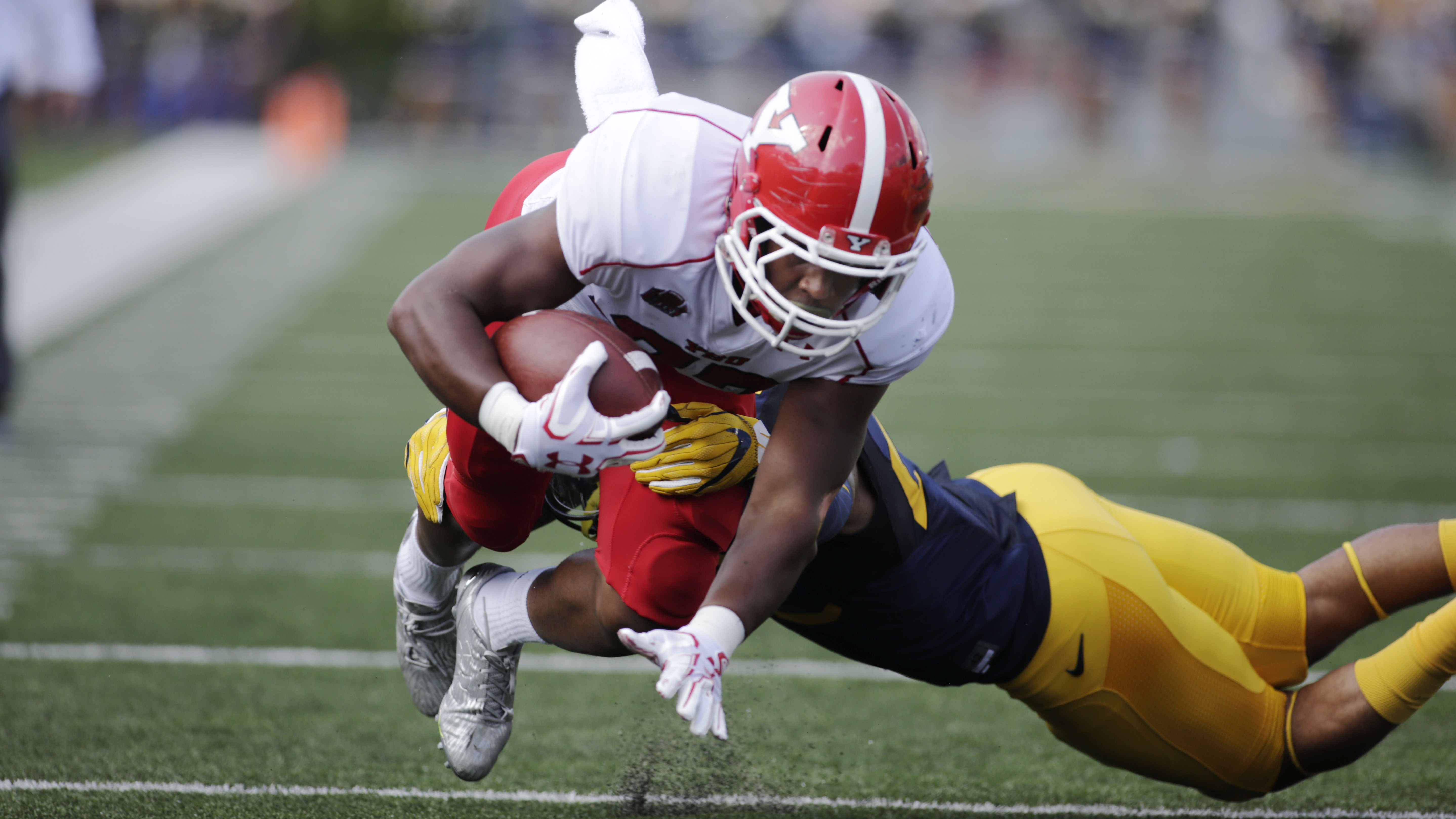 Youngstown State running back Tevin McCaster (37) is tackled by West Virginia safety Jarrod Harper (22) during the first half of an NCAA college football game, Saturday, Sept. 10, 2016, in Morgantown, W.Va. (AP Photo/Raymond Thompson)