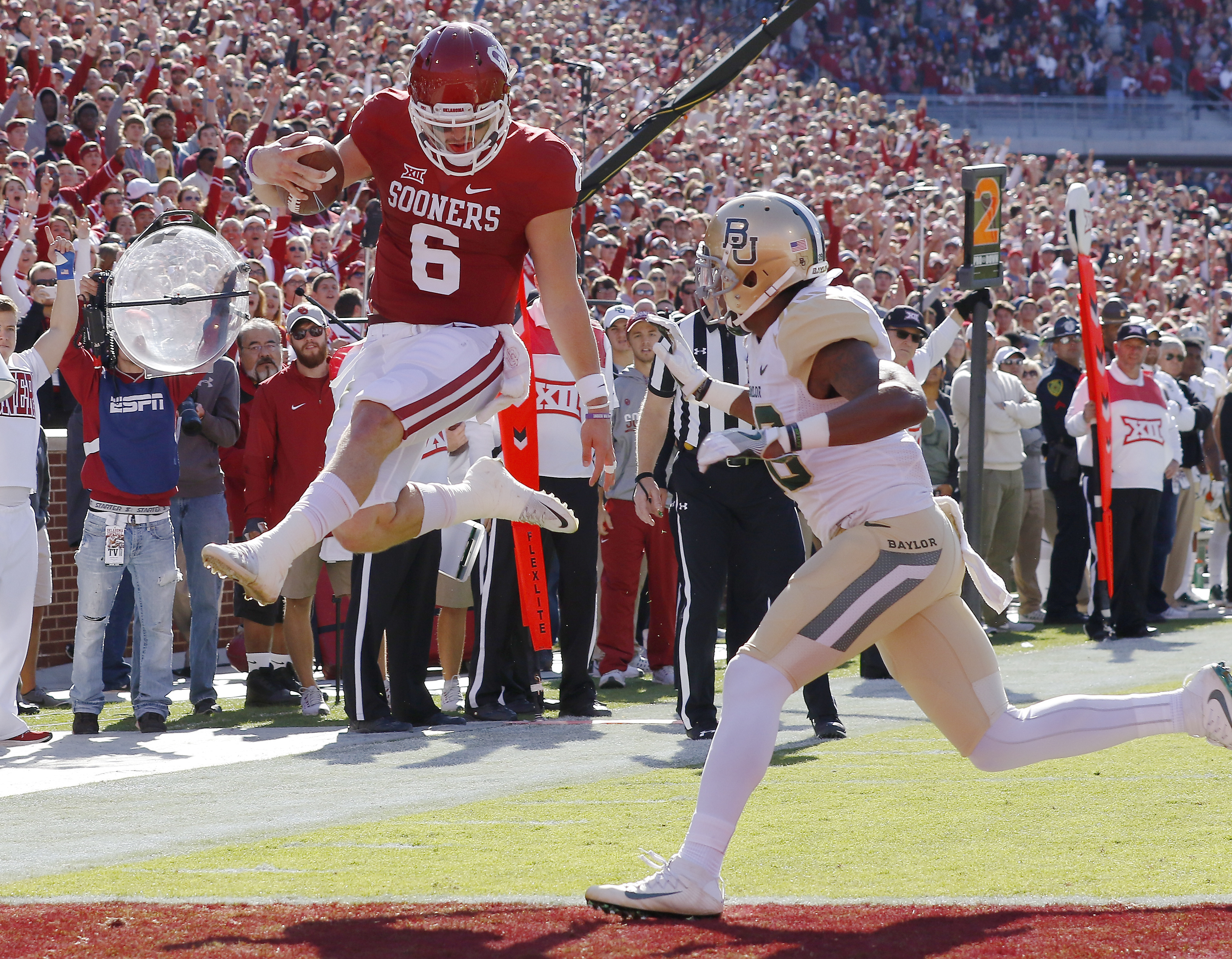 FILE - In this Nov. 12, 2016, file photo, Oklahoma quarterback Baker Mayfield (6) runs in for a touchdown ahead of Baylor safety Davion Hall (2) during the first half of a NCAA college football game in Norman, Okla. Mayfield was selected to the AP All Big