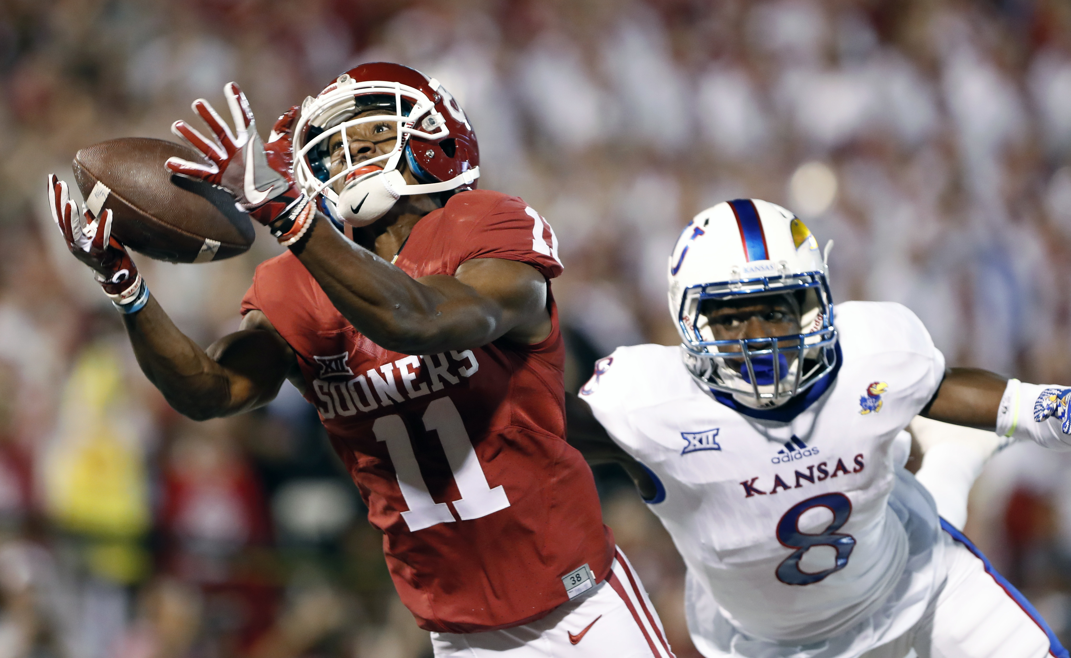 FILE - In this Oct. 29, 2016, file photo, Oklahoma wide receiver Dede Westbrook (11) makes a catch for a touchdown ahead of Kansas cornerback Brandon Stewart (8) during the first half of an NCAA college football game in Norman, Okla. Westbrook was selecte
