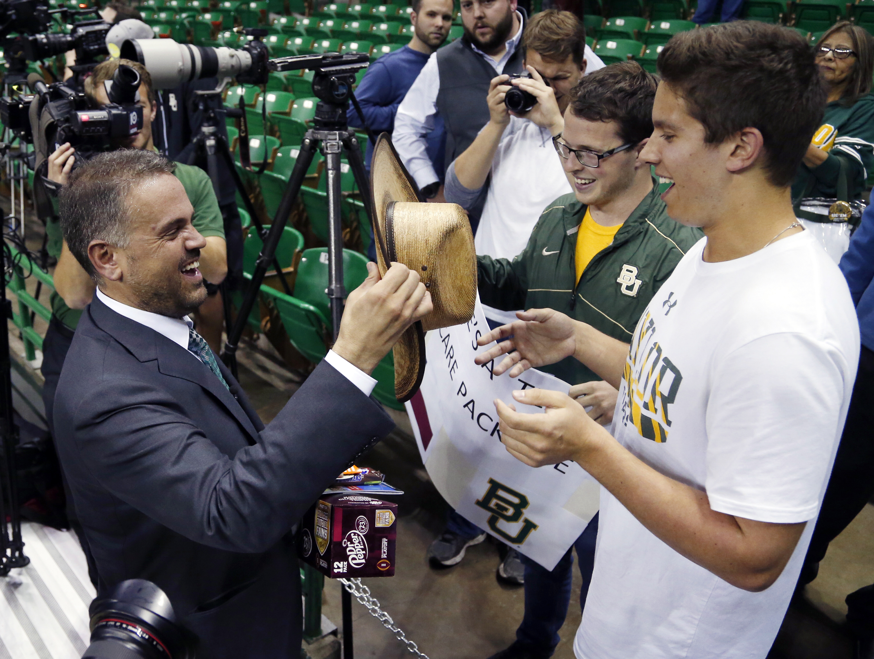 Baylor University's new football coach Matt Rhule, left, receives a cowboy hat from senior Caleb Simmons, right following a public event at the Ferrell Center, Wednesday, Dec. 7, 2016, in Waco, Texas. Rhule replaces Jim Grobe, who led the Bears to a 6-6 r