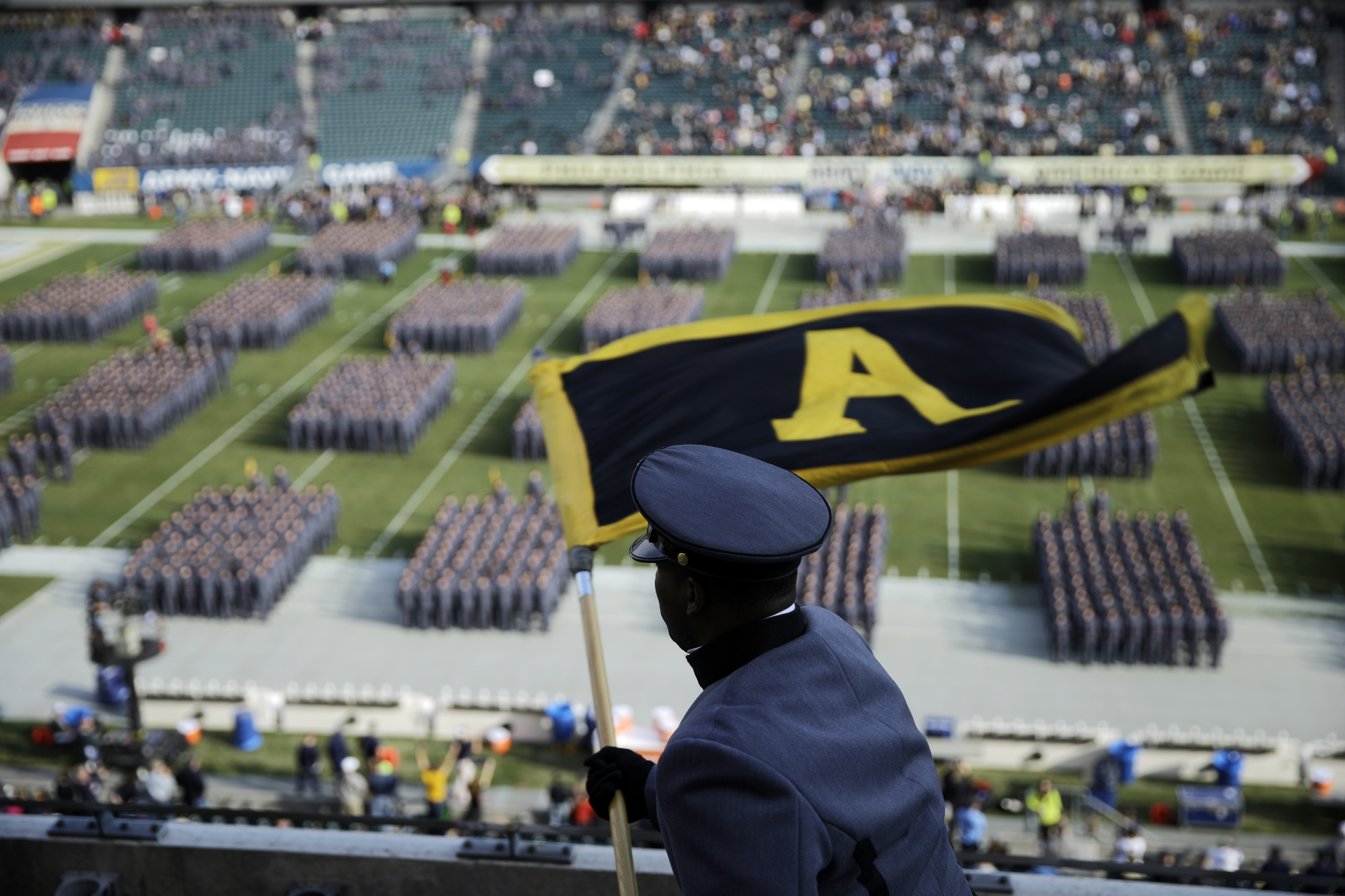 FILE - In this Dec. 12, 2015, file photo, an Army Cadet signals Cadets as they march onto the field before an NCAA college football game against Navy, in Philadelphia. When their football careers end, each player is obligated to begin serving in the milit