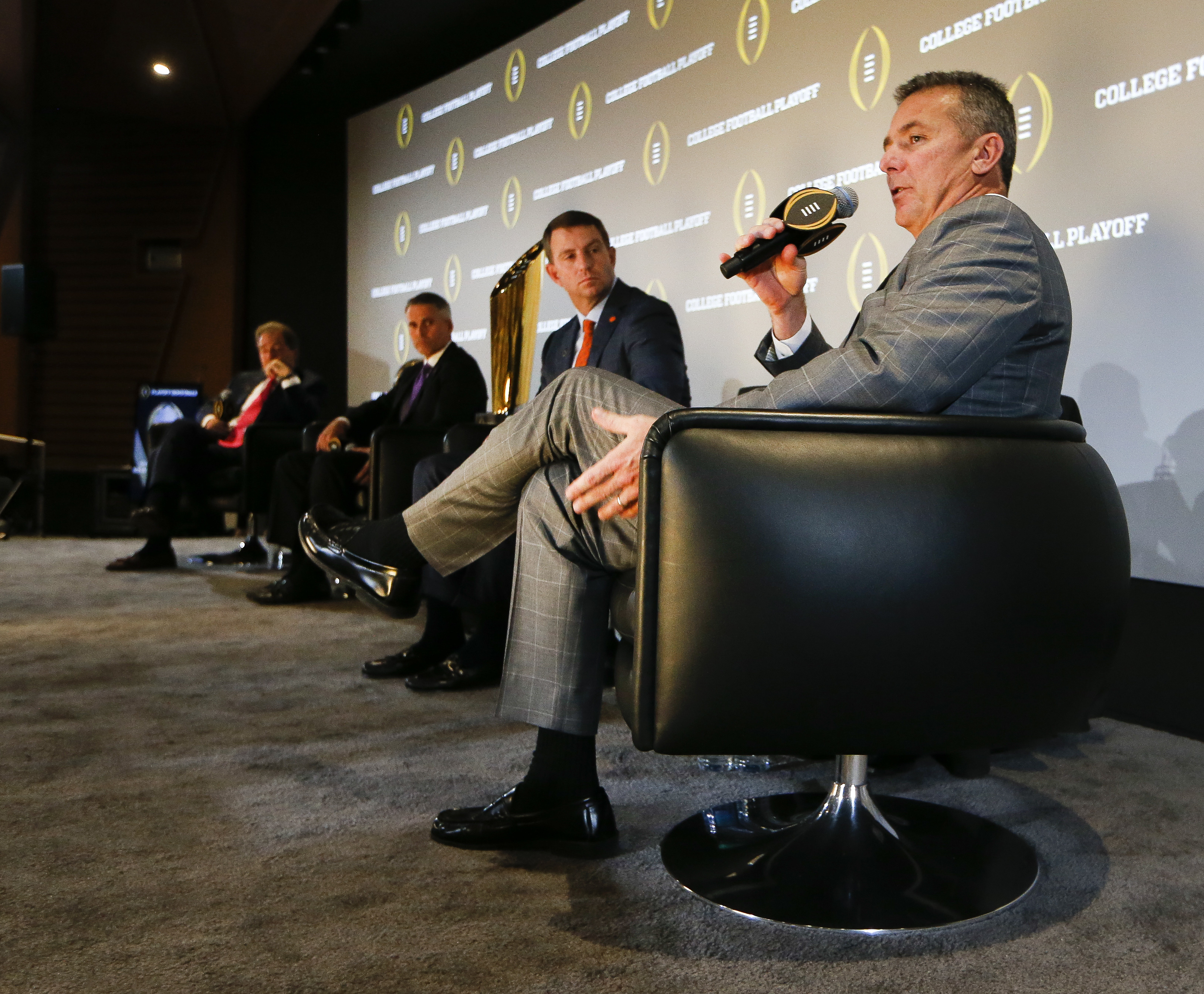Ohio State head football coach Urban Meyer speaks as coaches, from left, Nick Saban of Alabama, Chris Petersen of Washington and Dabo Sweeney of Clemson look on during a news conference with the all four coaches in the college football playoffs Thursday,