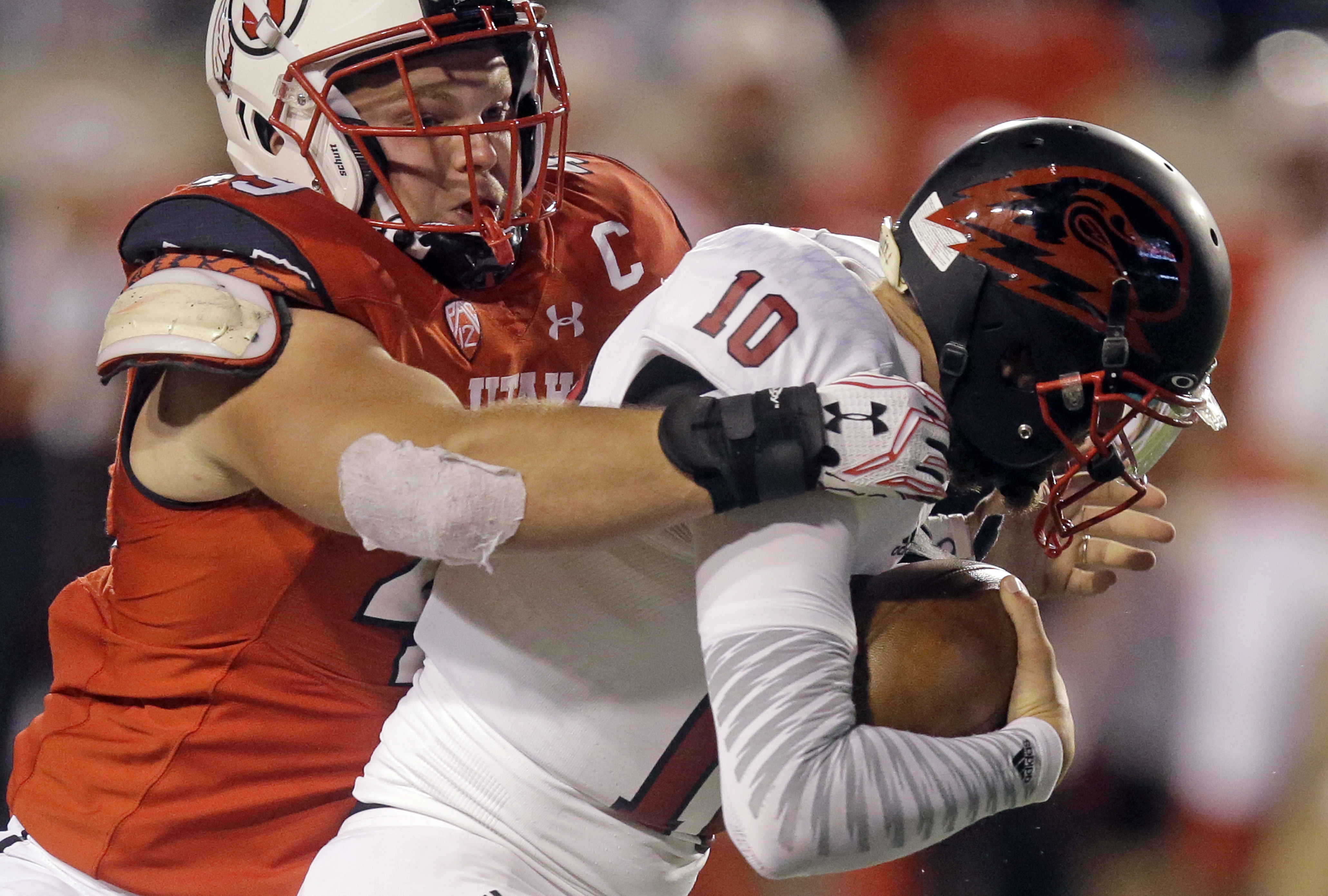 FILE - In this Sept. 1, 2016, file photo, Utah defensive end Hunter Dimick, left, sacks Southern Utah quarterback Tannon Pedersen (10) in the second half during an NCAA college football game in Salt Lake City. Dimick shared defensive player of the year ho