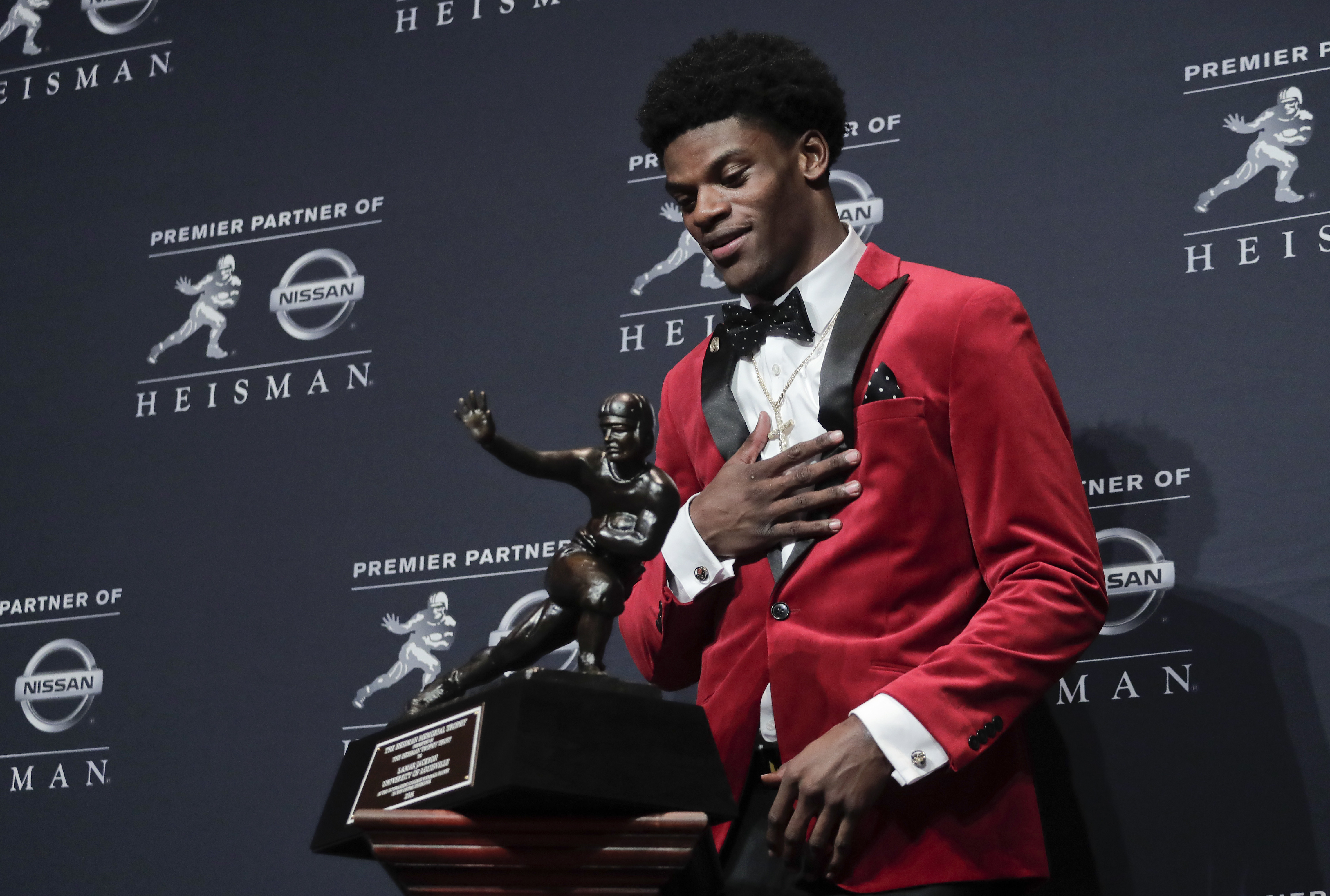 Louisville's Lamar Jackson prepares to pick up the the Heisman Trophy after winning the Heisman Trophy award, Saturday, Dec. 10, 2016, in New York. (AP Photo/Julie Jacobson)