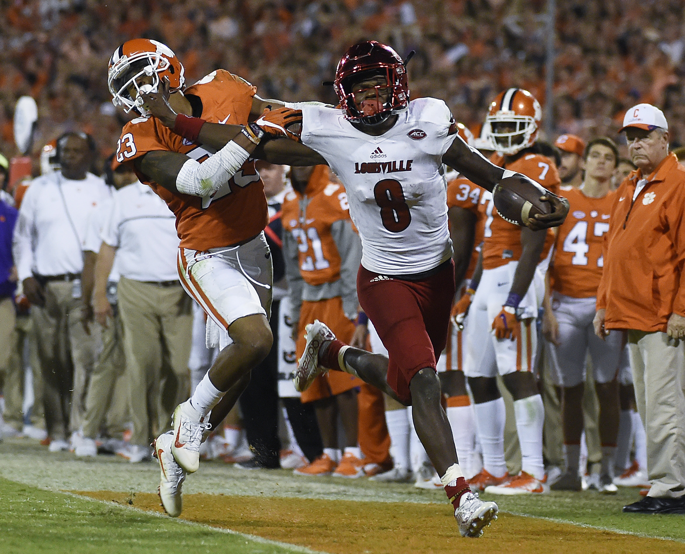 FILE - In this Oct. 1, 2016, file photo, Louisville quarterback Lamar Jackson (8) stiff-arms Clemson safety Van Smith (23) as he goes out of bounds during the second half of an NCAA college football game, in Clemson, S.C. The AP college football  Player o