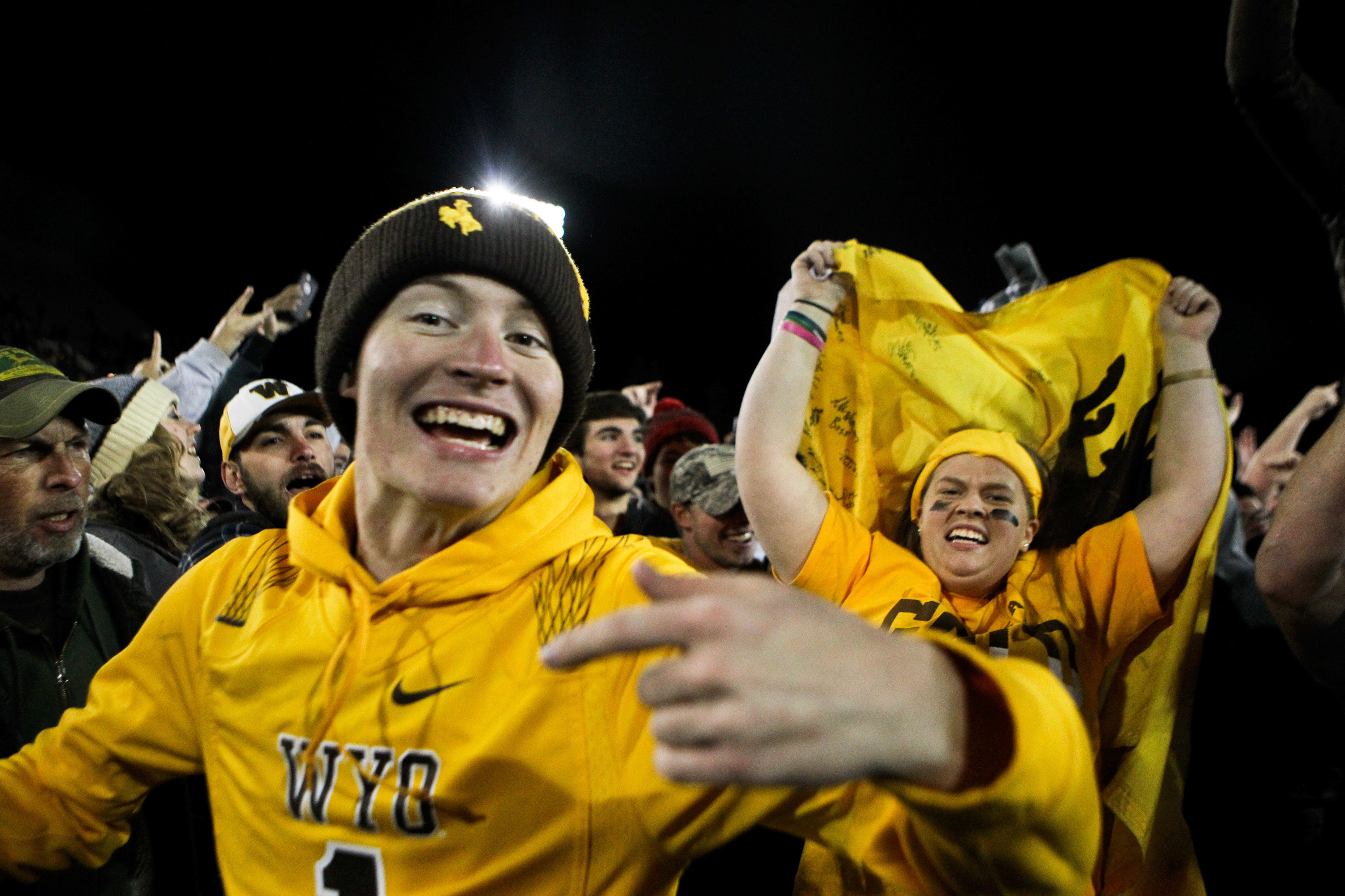 FILE - In this Saturday, Nov. 19, 2016, file photo, Wyoming fans react after the team defeated San Diego State 34-33 in Laramie, Wyo. By all accounts, Wyoming's football program has made a remarkable turnaround from a team that last had a winning season i