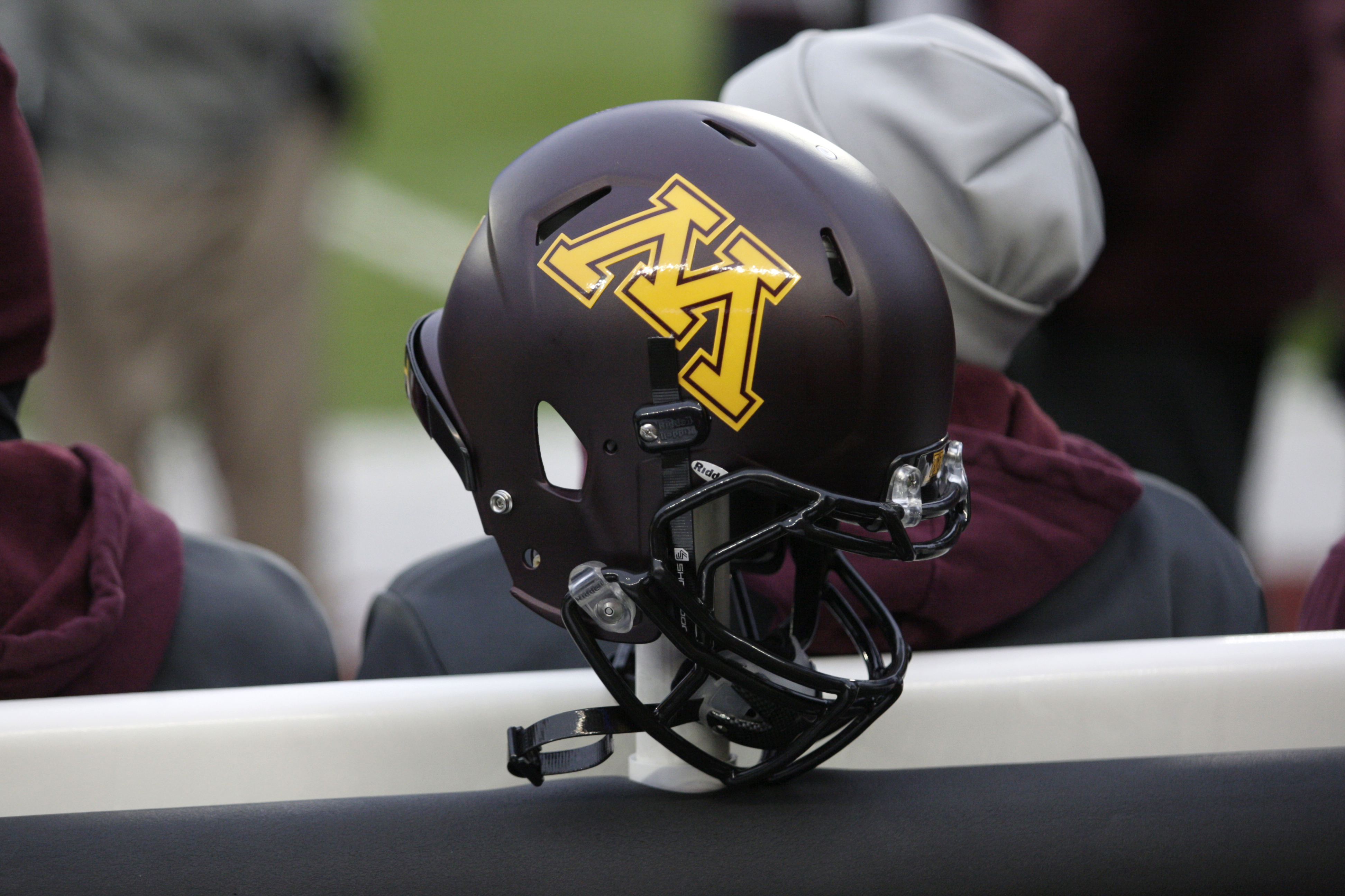 FILE - In this Nov. 24, 2012, file photo, a Minnesota helmet hangs on a sideline heater during an NCAA college football game against Michigan State, in Minneapolis. Ten Minnesota football players were suspended this week following a fresh investigation in