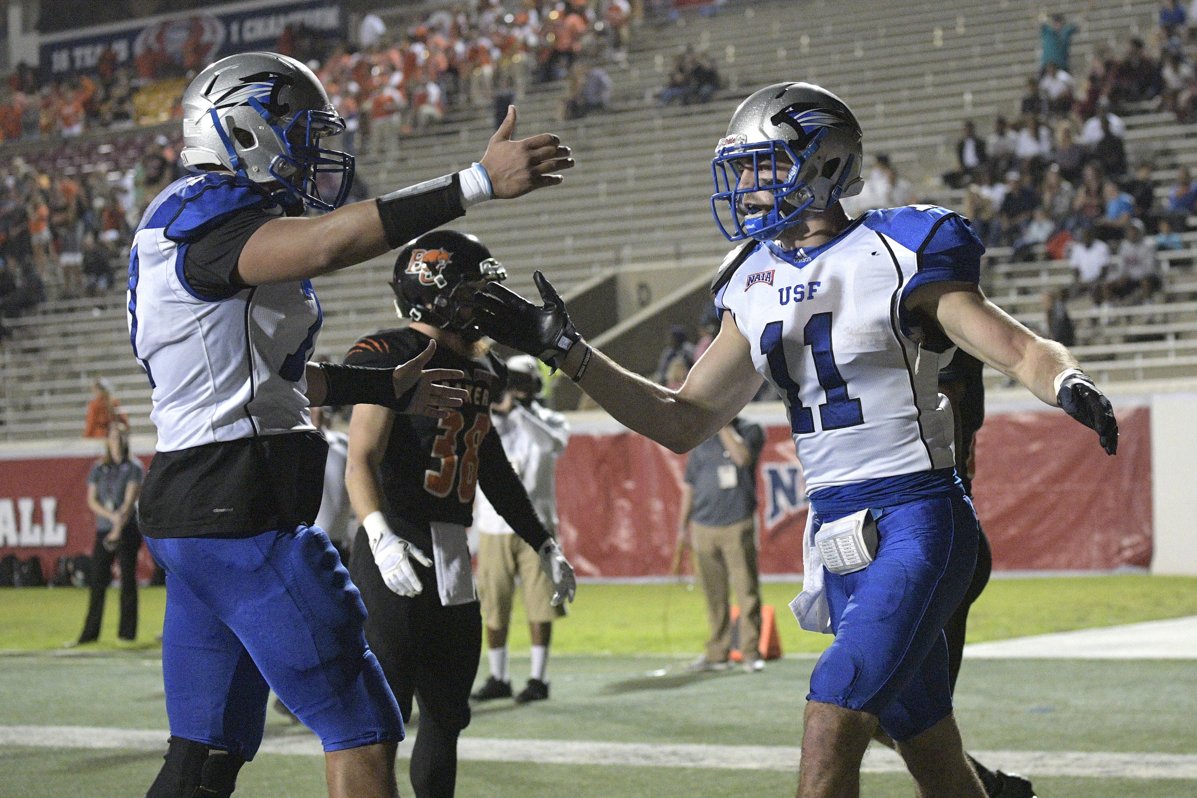 Saint Francis receiver Seth Coate (11) is congratulated by offensive lineman Jaylen Gamble, left, after catching a 5-yard pass for a touchdown during the first half of the NAIA championship football game against Baker in Daytona Beach, Fla., Saturday, Dec