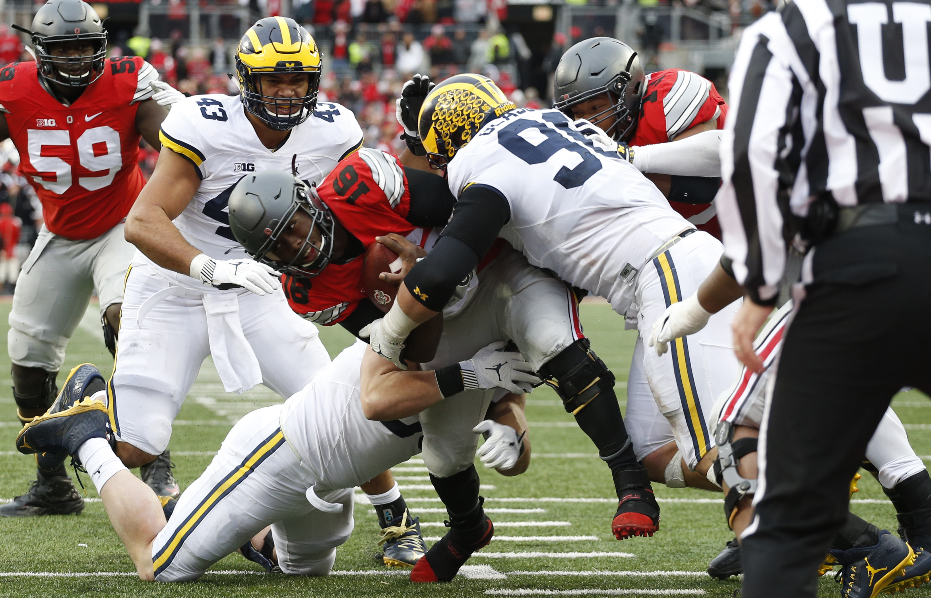 FILE - In this Nov. 26, 2016, file photo, Ohio State quarterback J.T. Barrett, center, runs for a first down as Michigan defendersChris Wormley, left, Matthew Godin, and Ryan Glasgow make the tackle during the second half of an NCAA college football game,