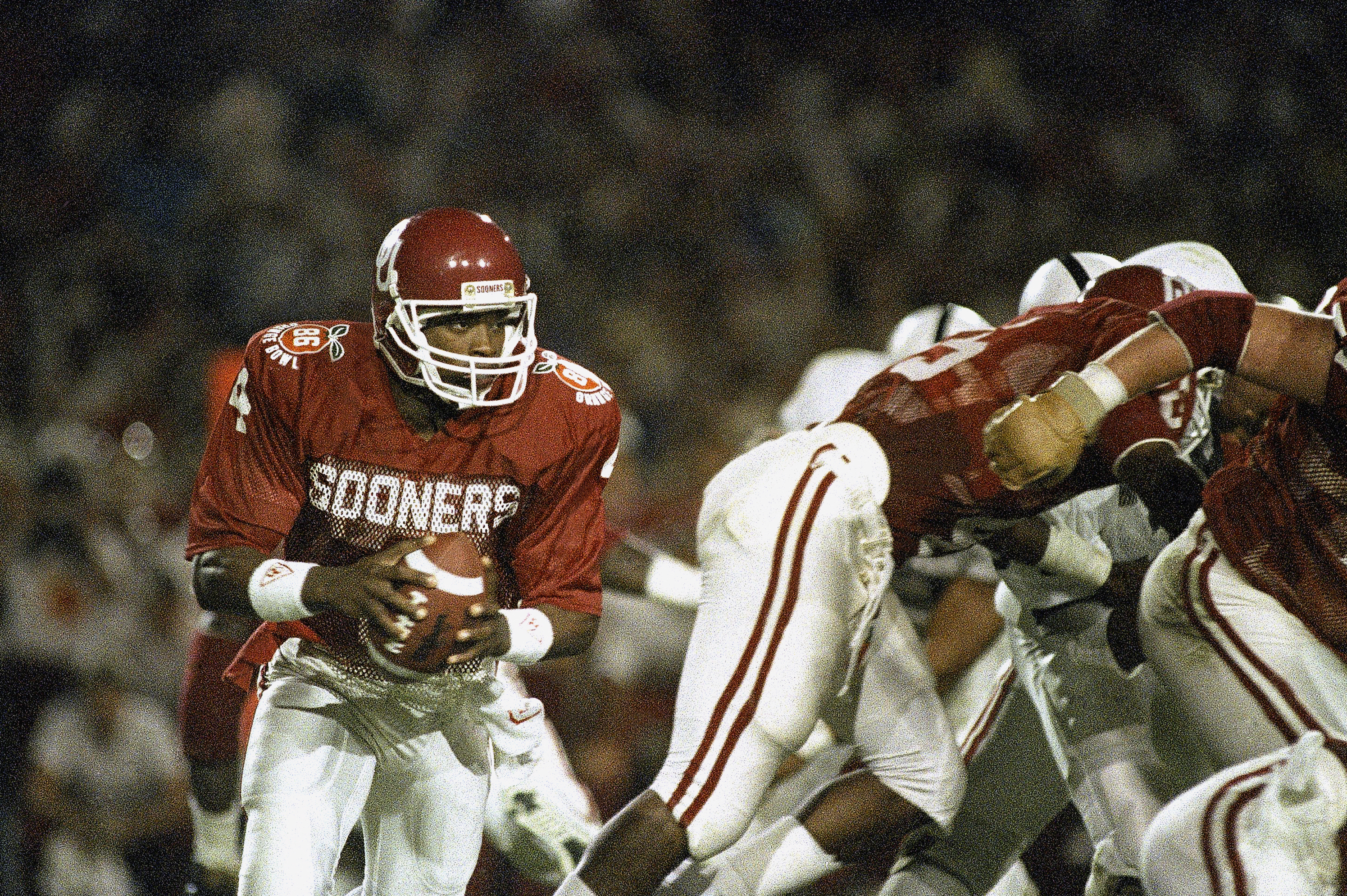 FILE - In this Jan. 1, 1986 file photo, University of Oklahoma quarterback Jamelle Holieway (4) looks for an open man as his team battles Penn State University in the Orange Bowl in Miami. Holieway dazzled the college football world as a true freshman who