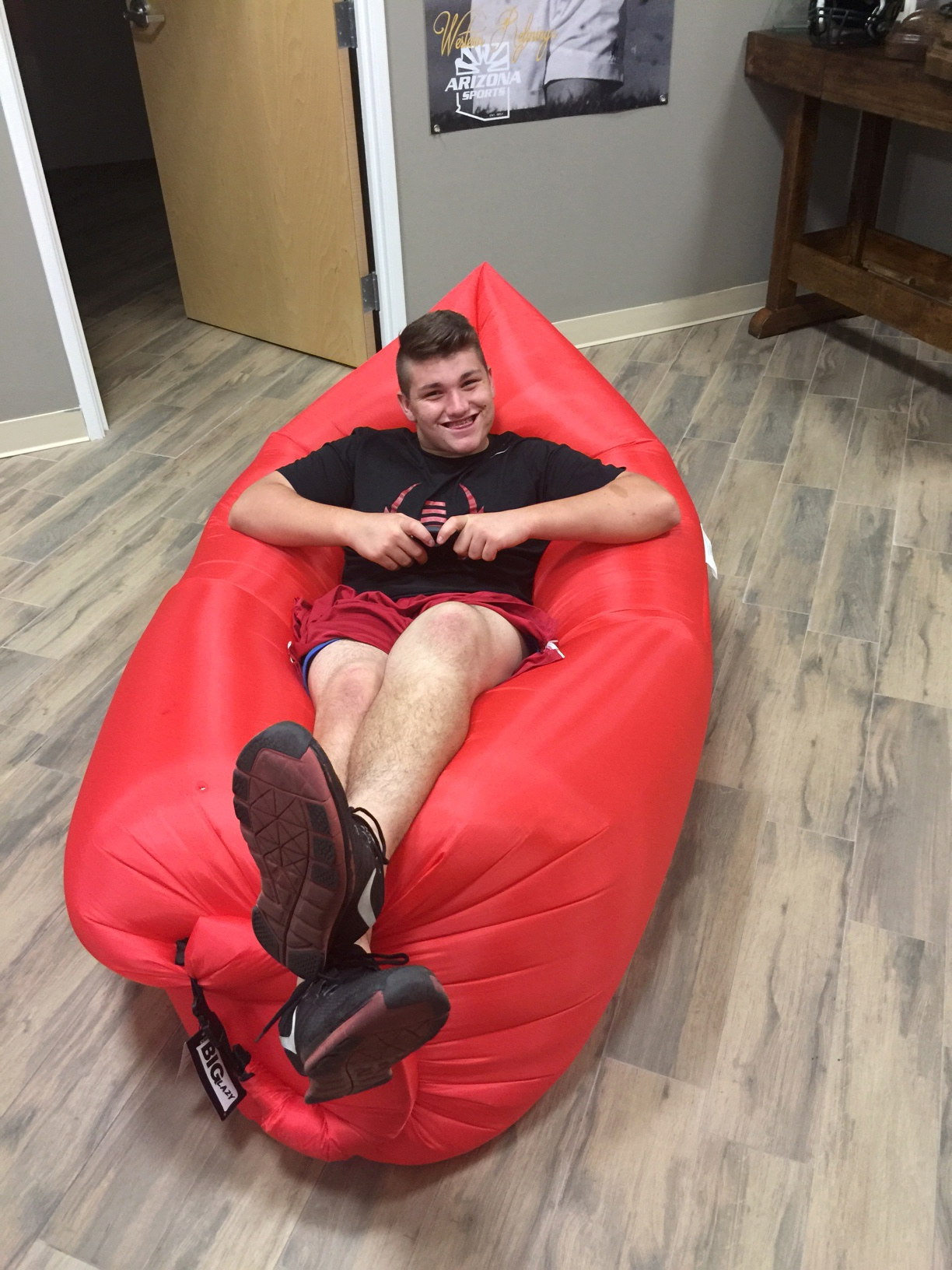"In this photo provided by NOVA Home Loans Arizona Bowl, a worker from the Arizona Bowl shows off one of the inflatable ""Big Lazy"" couches that is part of bowl gifts being given to players for the Dec. 29 game. The couch is one of the unique items as the 4"