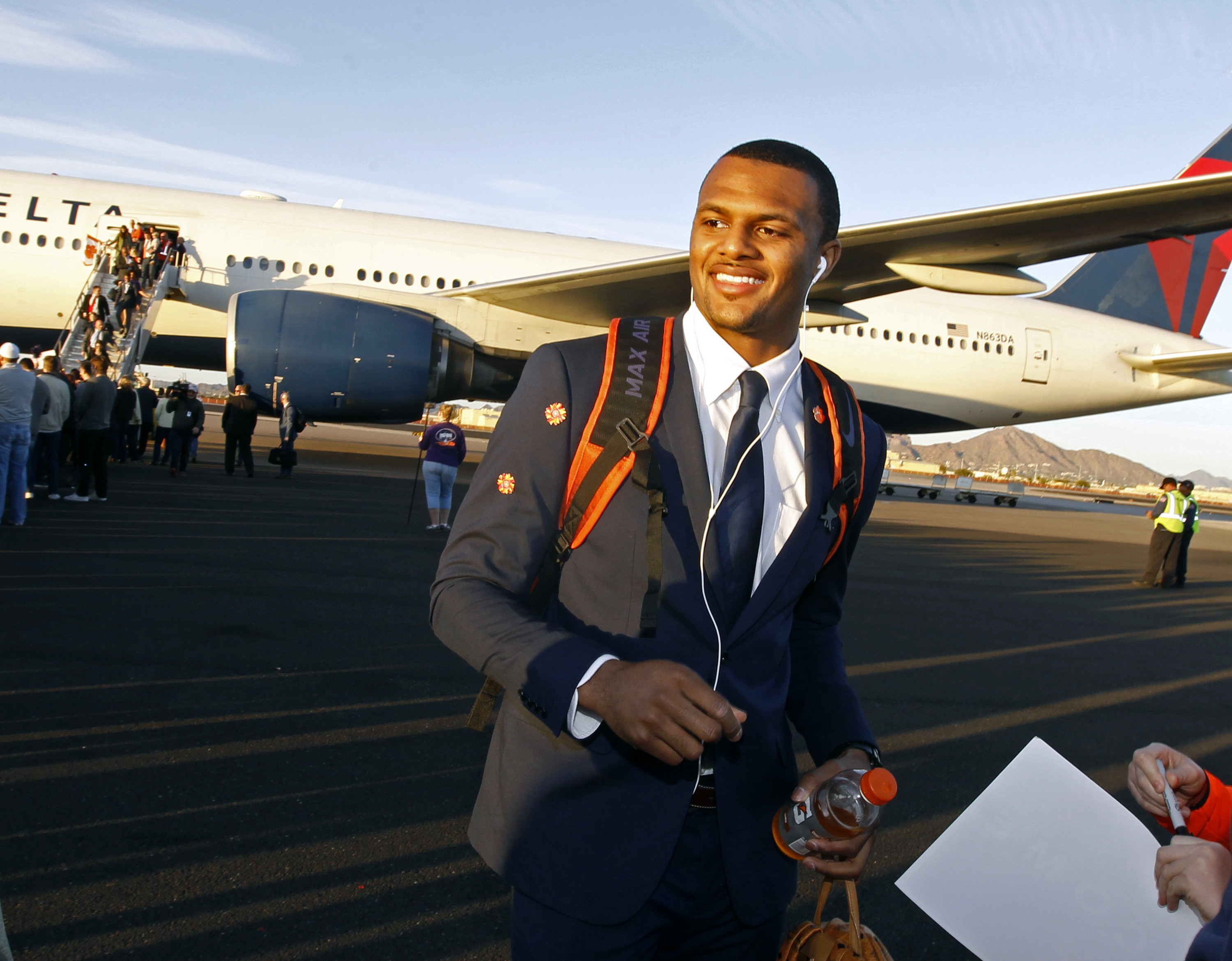 Clemson quarterback Deshaun Watson walks across the tarmac after arriving with his team at Phoenix Sky Harbor Airport on Monday, Dec. 26, 2016, in Phoenix. Clemson will play Ohio State in the Fiesta Bowl as part of the college football playoff semifinal o