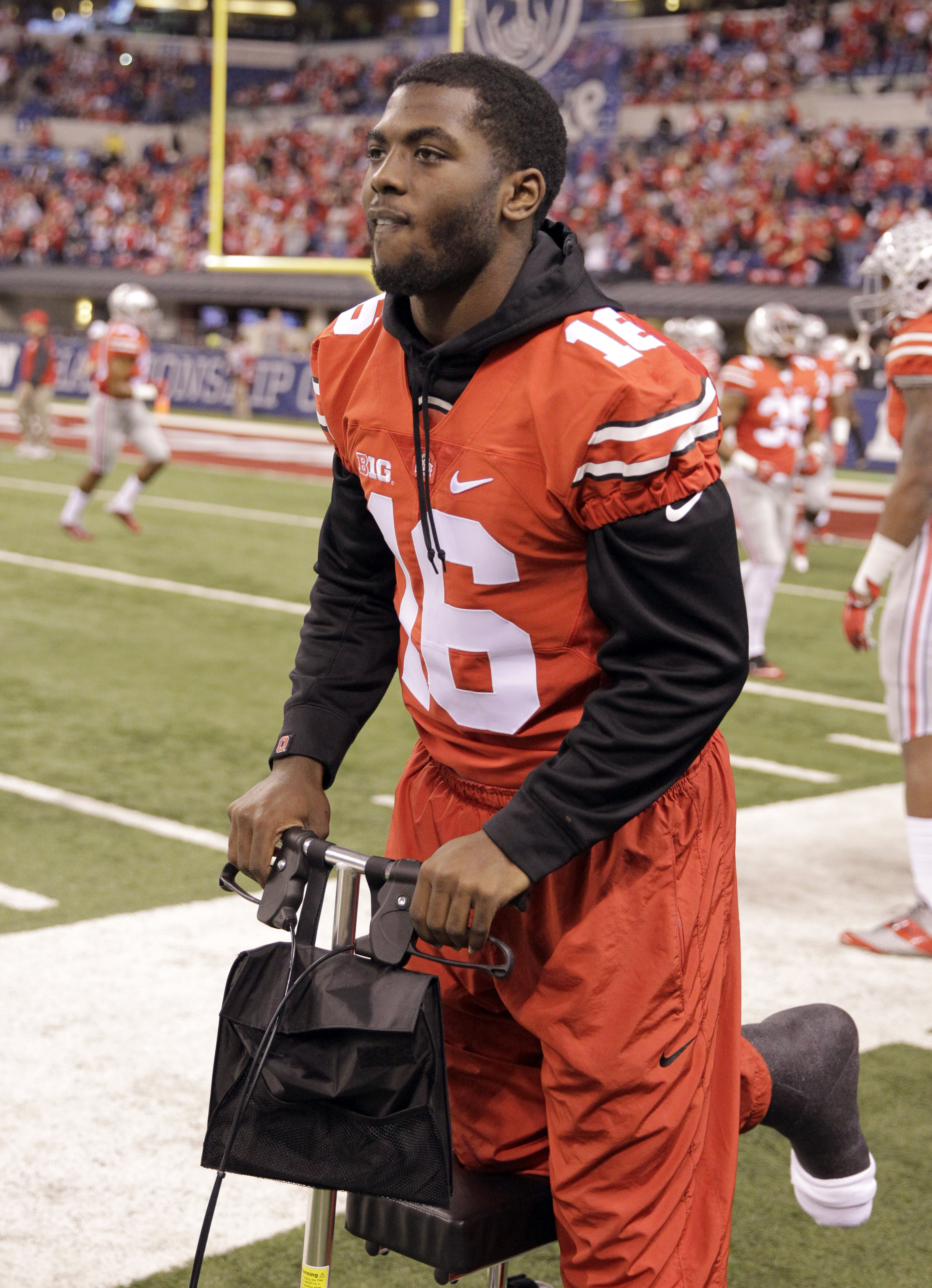 FILE - In a Saturday, Dec. 6, 2014 file photo, injured Ohio State quarterback J.T. Barrett is seen on the sidelines before the start of the Big Ten Conference championship NCAA college football game between Ohio State and Wisconsin, in Indianapolis. In 20