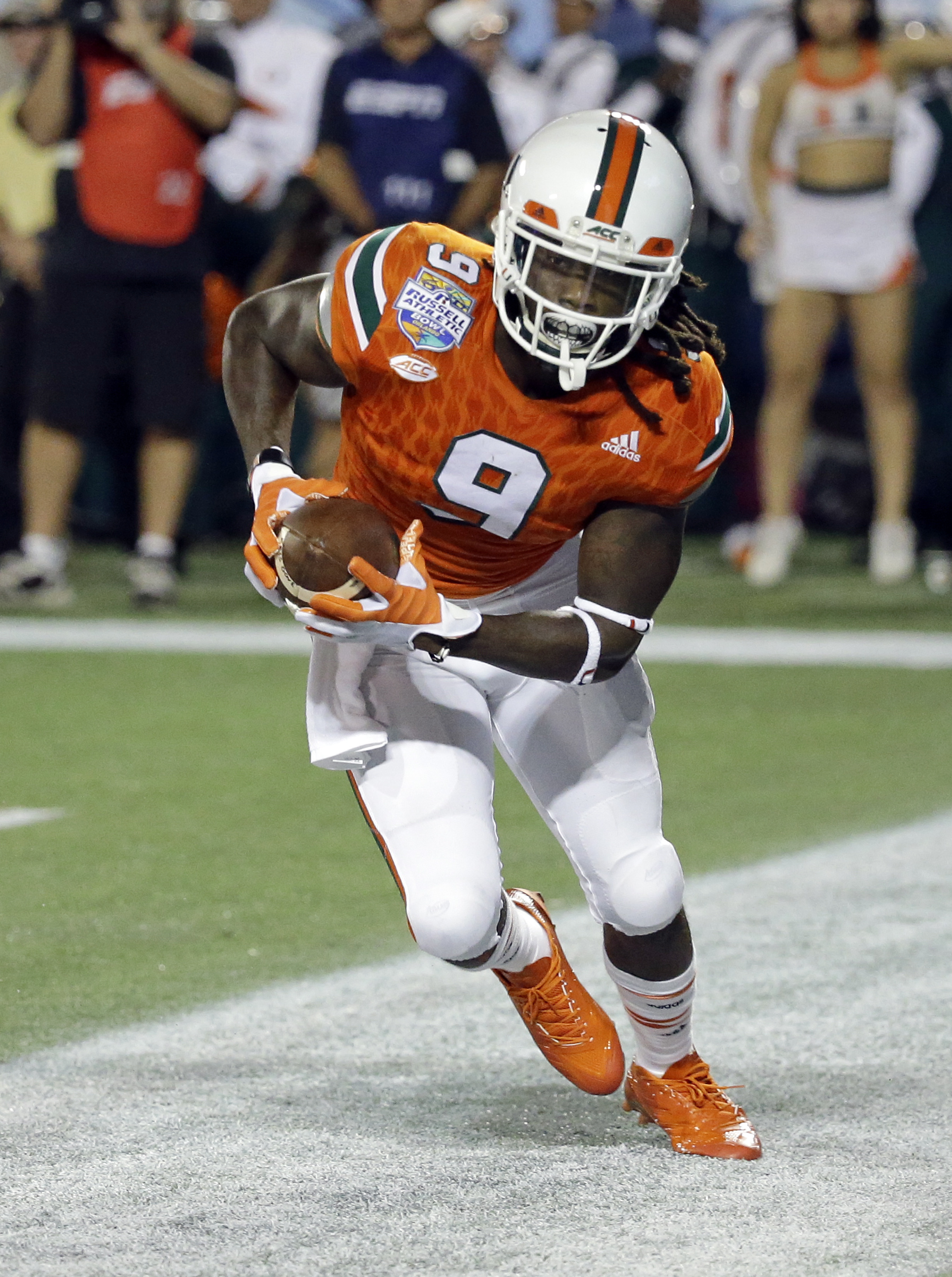 Miami wide receiver Malcolm Lewis (9) catches a pass in the end zone for a 3-yard touchdown against West Virginia during the first half of the Russell Athletic Bowl NCAA college football game, Wednesday, Dec. 28, 2016, in Orlando, Fla. (AP Photo/John Raou
