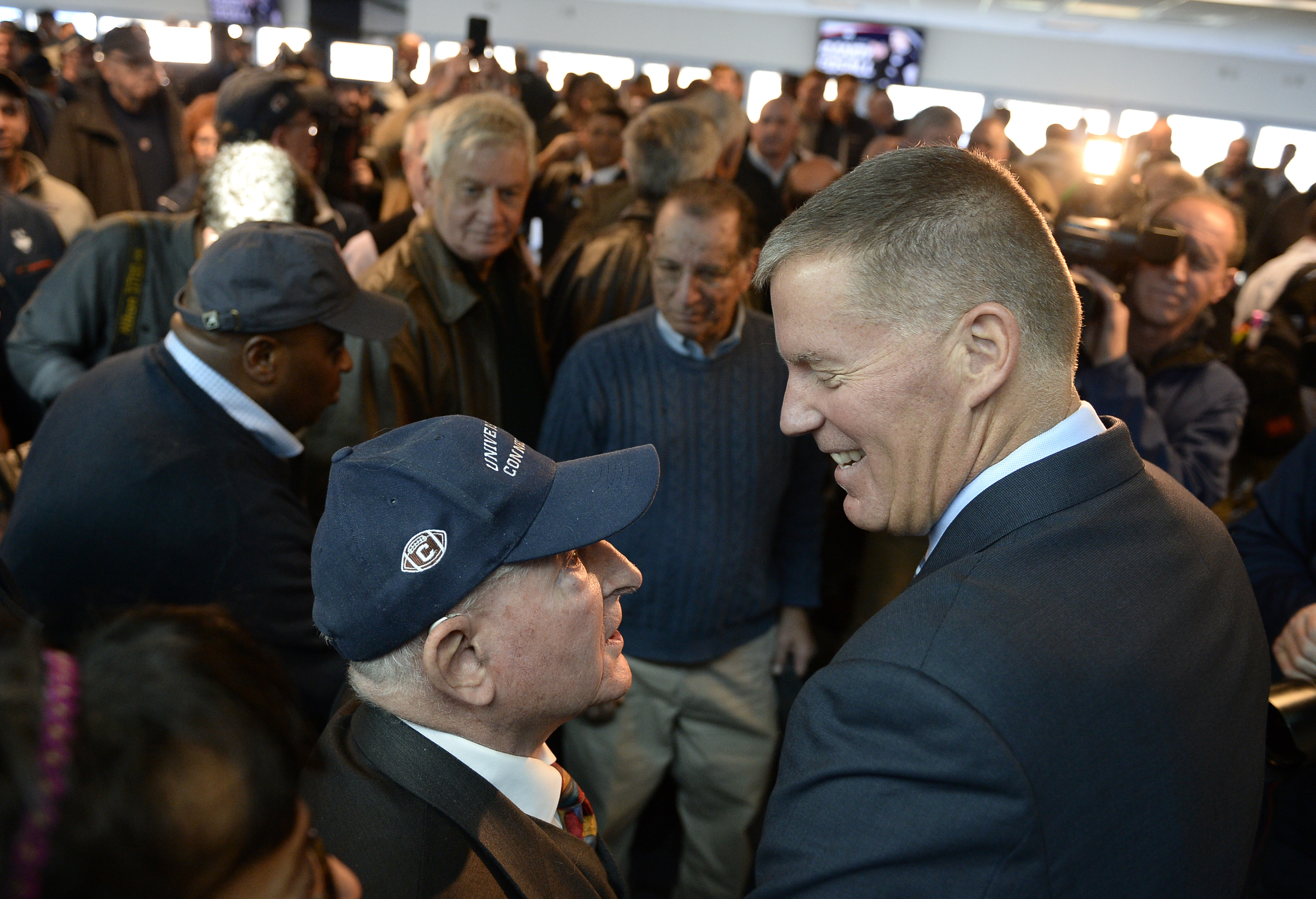 Newly announced Connecticut football head coach Randy Edsall talks with fan Milton Porter of Hebron, Conn., left, after an NCAA college football news conference at Pratt & Whitney Stadium at Rentschler Field, Friday, Dec. 30, 2016, in East Hartford, Conn.