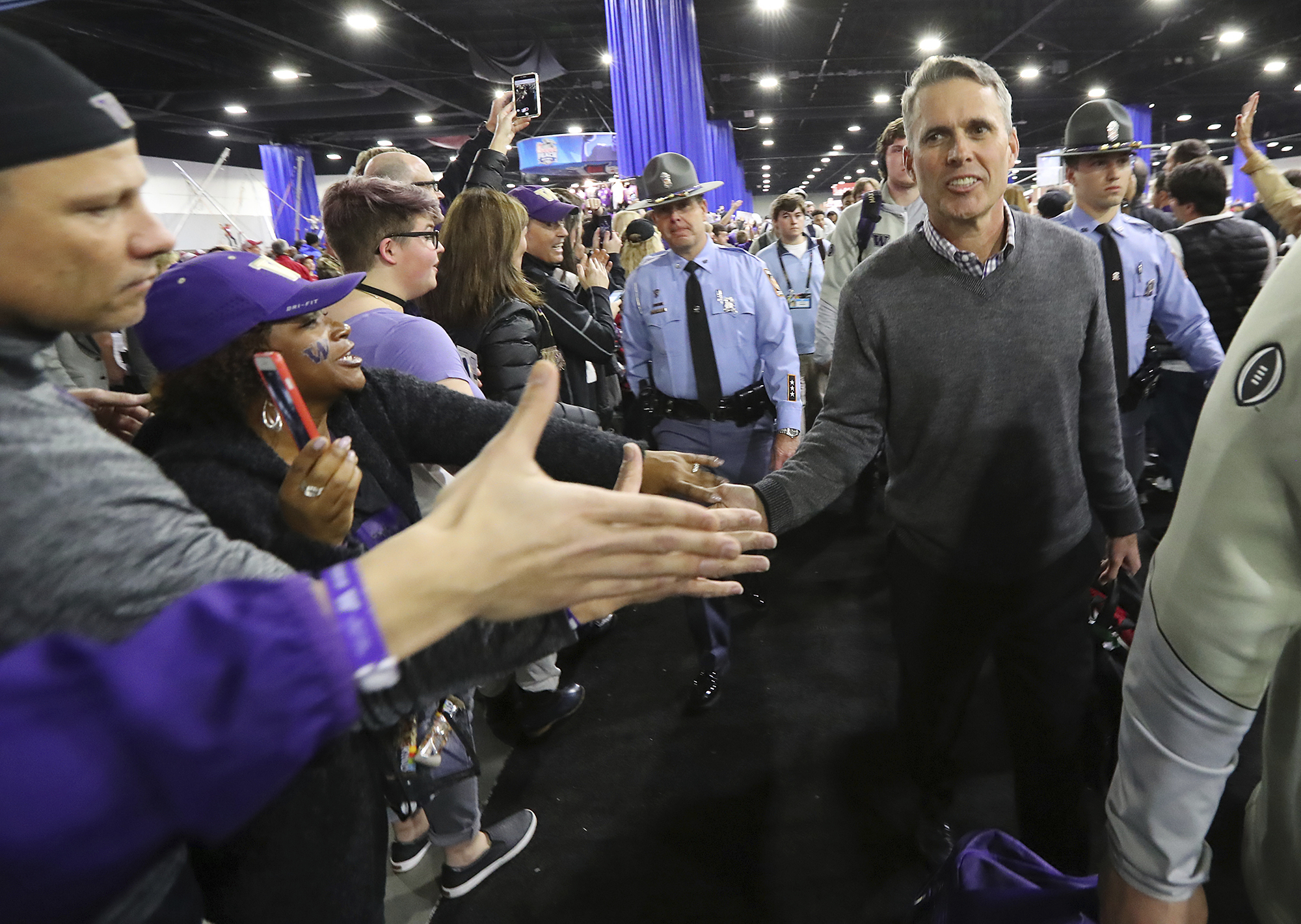 Washington head coach Chris Petersen gets five from fans during the team walk through Fan Fest to the Peach Bowl NCAA college football playoff game against Alabama at the Georgia Dome, Saturday, Dec. 31, 2016, in Atlanta. (Curtis Compton/Atlanta Journal-C
