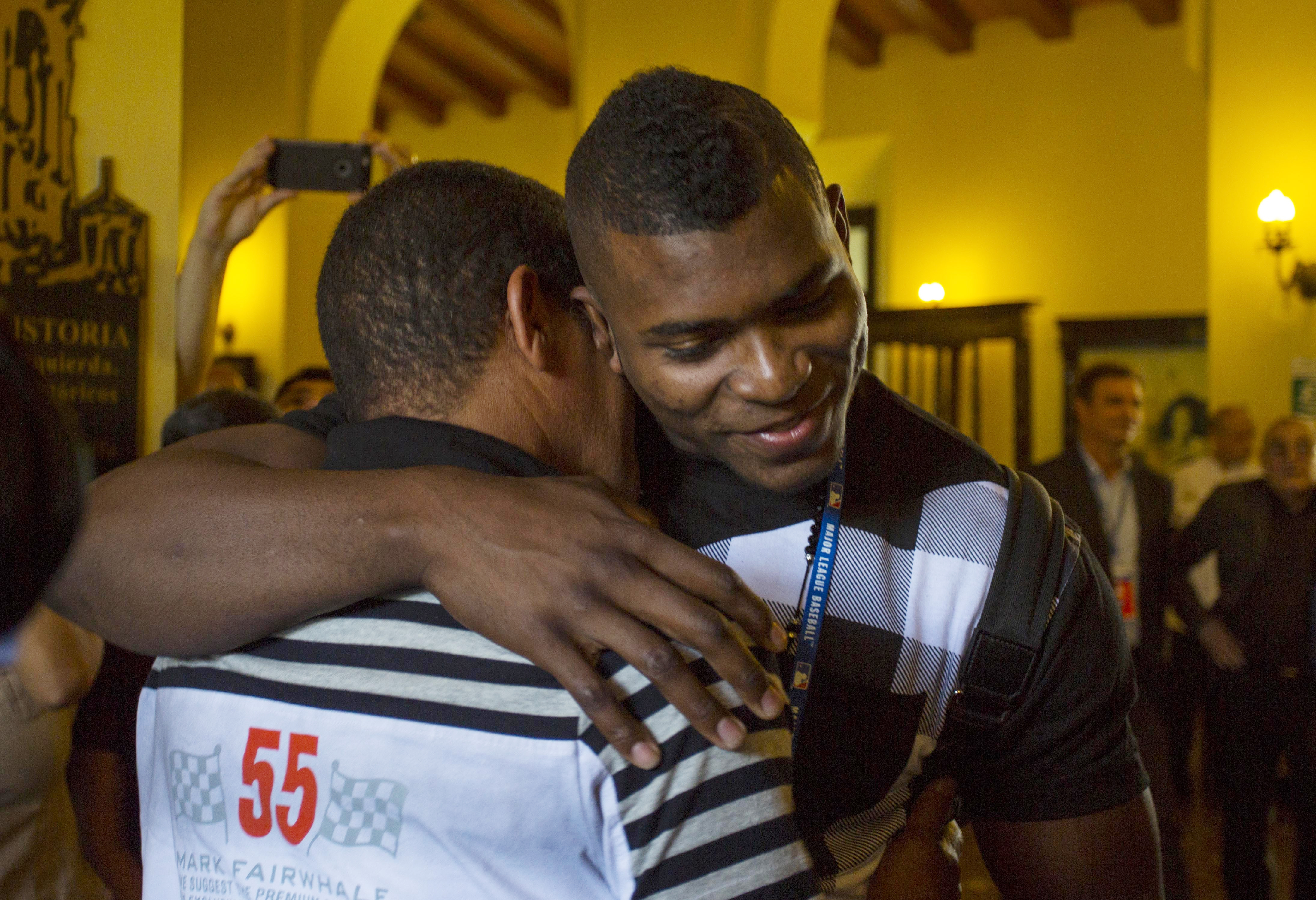 Los Angeles Dodgers outfielder Yasiel Puig, right, hugs his former coach Juan Arechavaleta as he arrives to Hotel Nacional in Havana, Cuba, Tuesday, Dec. 15, 2015. A lineup of Cuban baseball superstars including some of the most famous defectors in recent