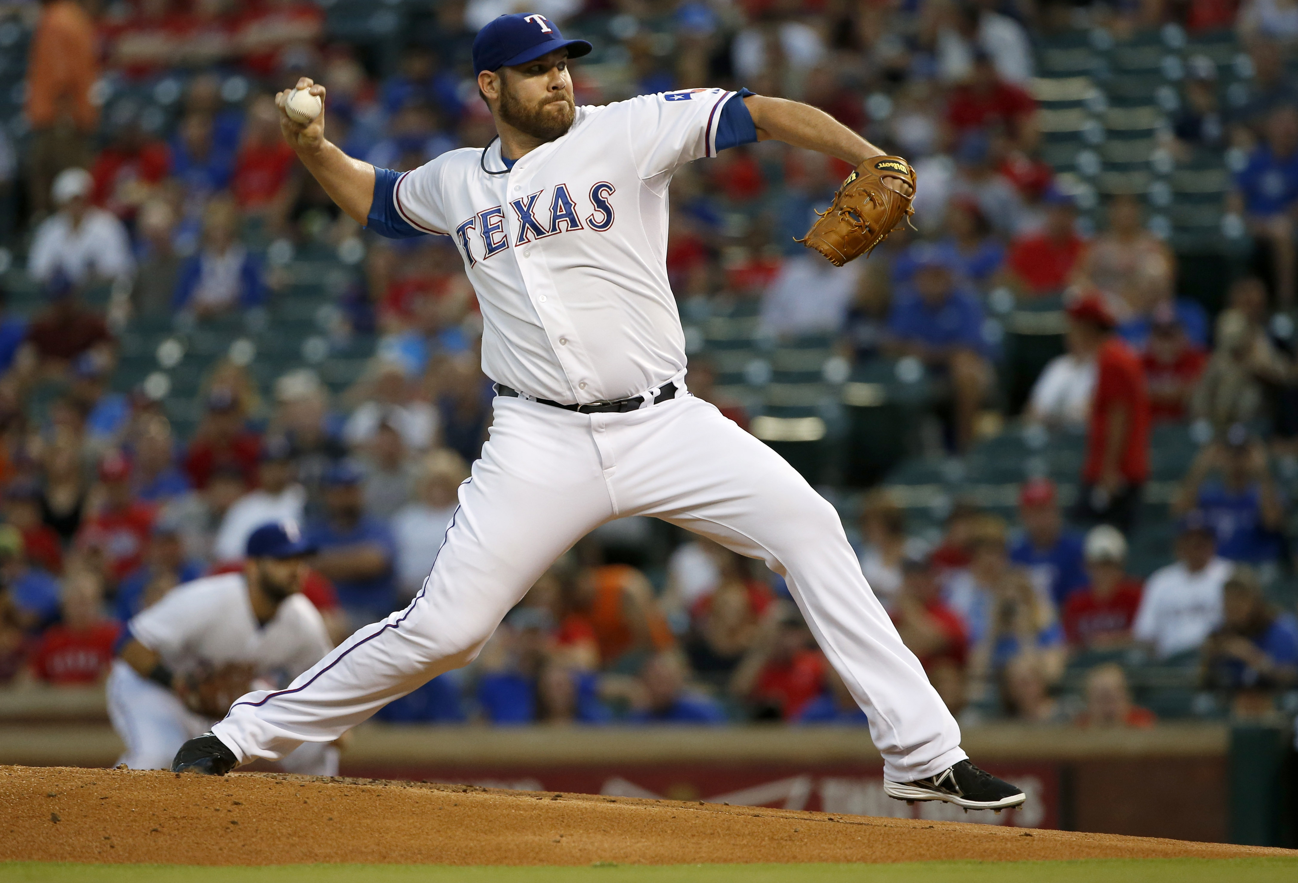 FILE - In this Sept. 18, 2015, file photo, Texas Rangers starting pitcher Colby Lewis works against the Detroit Tigers in the first inning of a baseball game, in Arlington,Texas. A person familiar with the deal says the Rangers and veteran pitcher Colby L