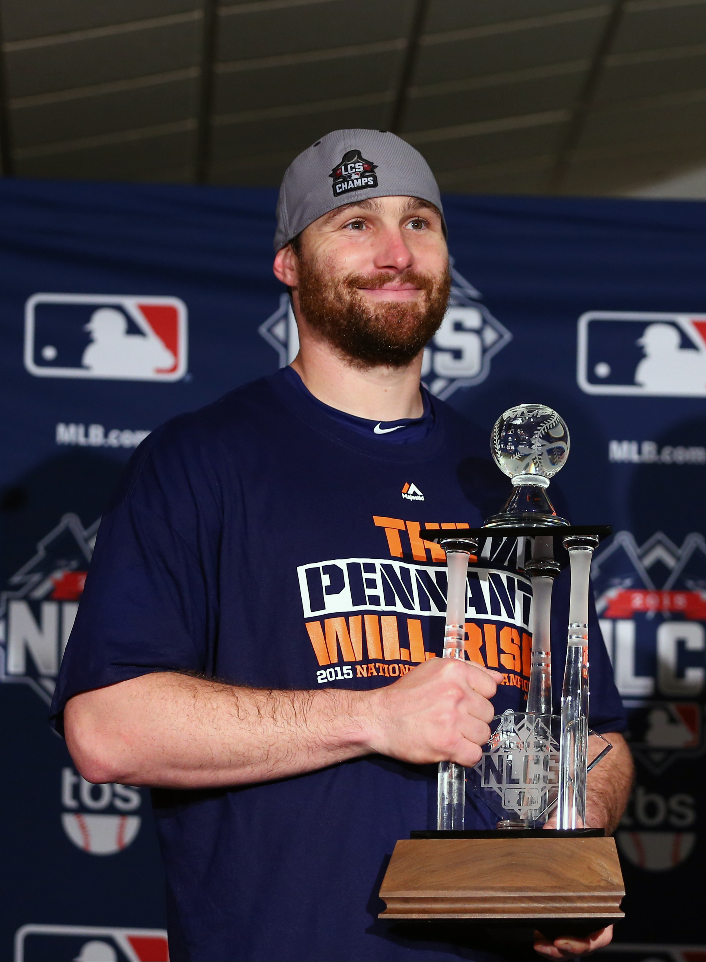 New York Mets' Daniel Murphy holds his MVP trophy after Game 4 of the National League baseball championship series against the Chicago Cubs Wednesday, Oct. 21, 2015, in Chicago. The Mets won 8-3 to advance to the World Series. (Elsa/Pool Photo via AP)