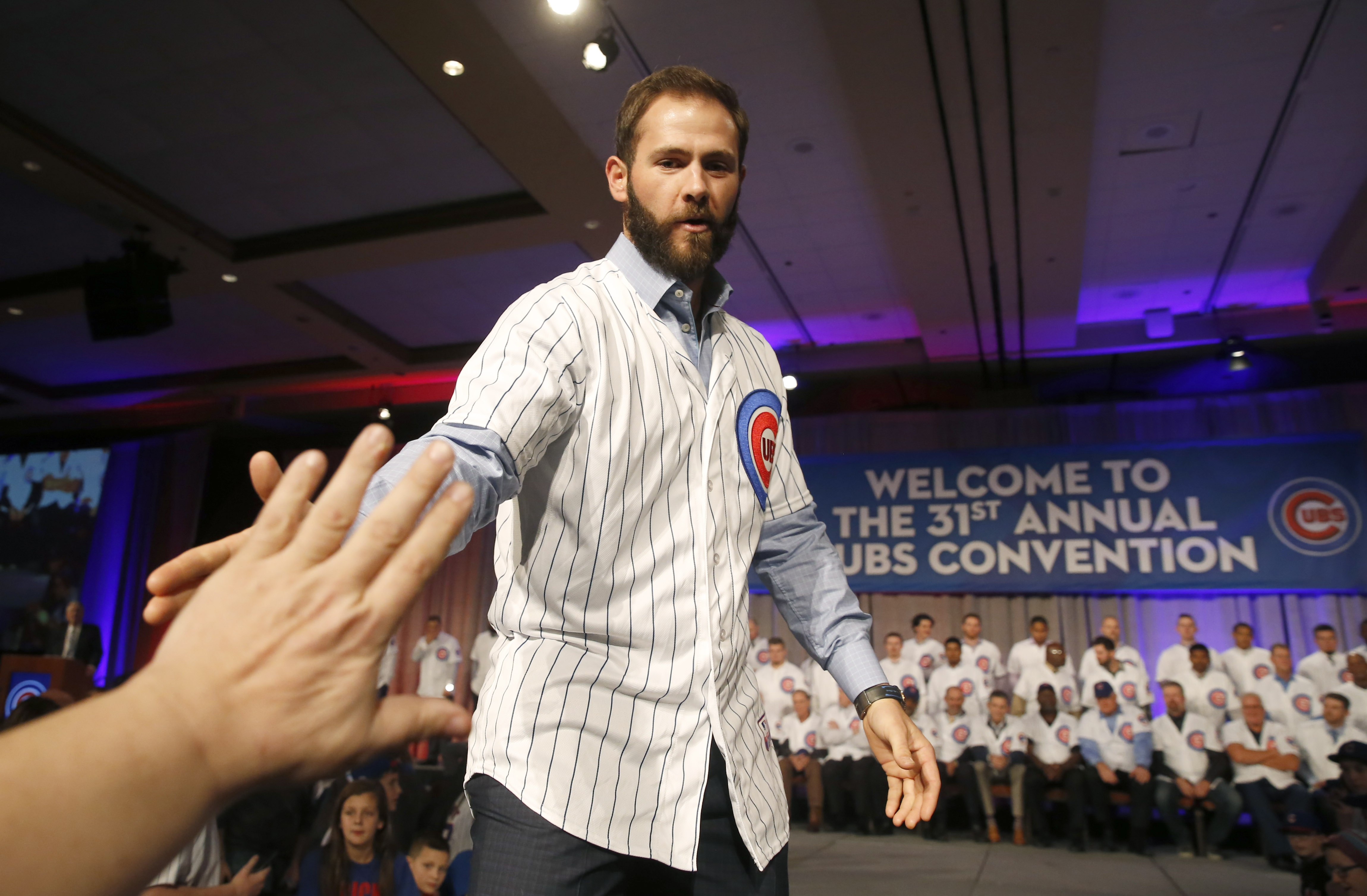 Chicago Cubs starting pitcher Jake Arrieta slaps hands with a fan during the team's annual baseball convention Friday, Jan. 15, 2016, in Chicago. (AP Photo/Charles Rex Arbogast)
