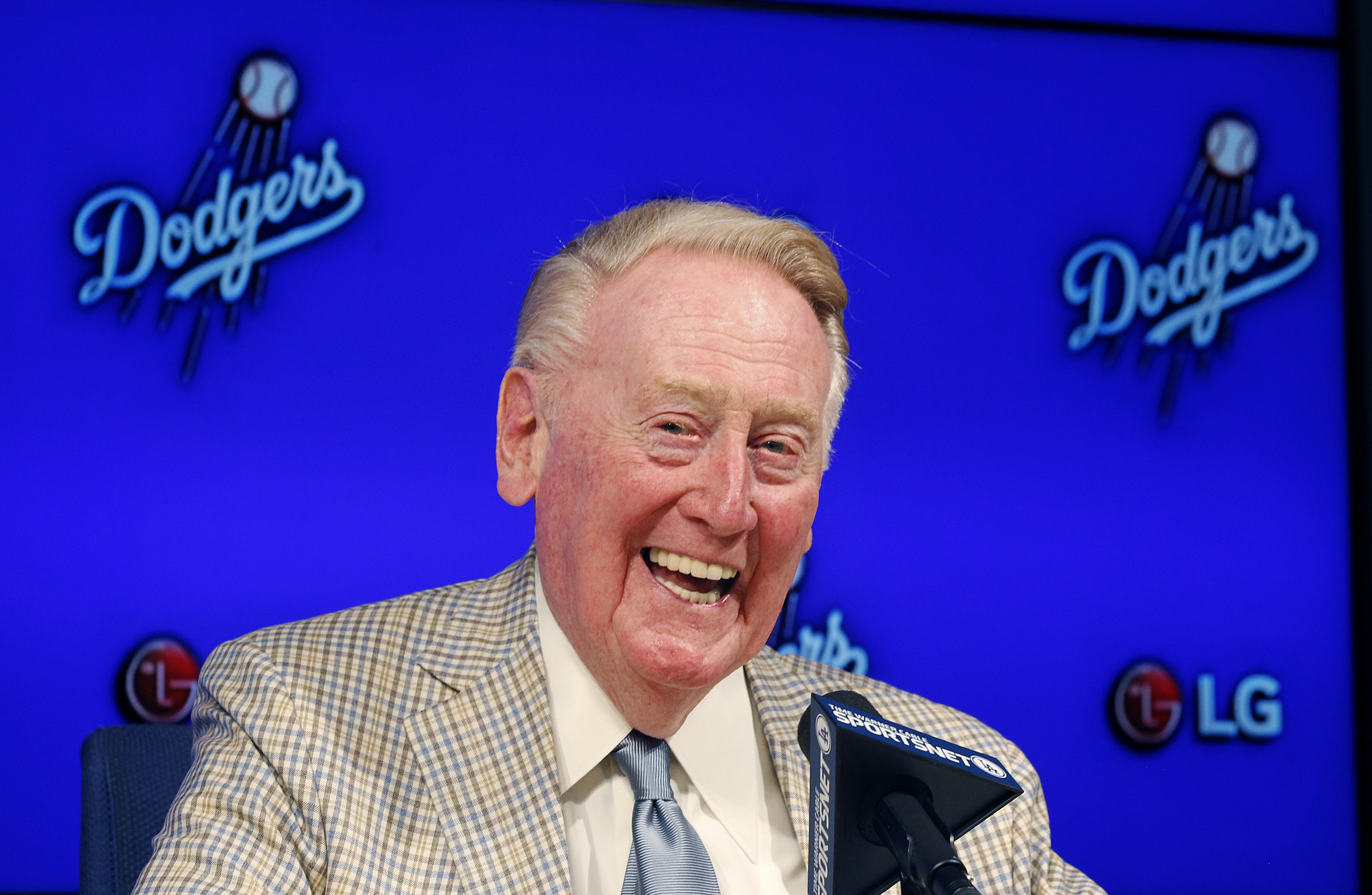 FILE - In this Aug. 29, 2015, file photo, Los Angeles Dodgers Hall of Fame broadcaster Vin Scully announces he will return to broadcast his 67th baseball season in 2016 during a news conference in Los Angeles. Visitors to Dodger Stadium will eventually be