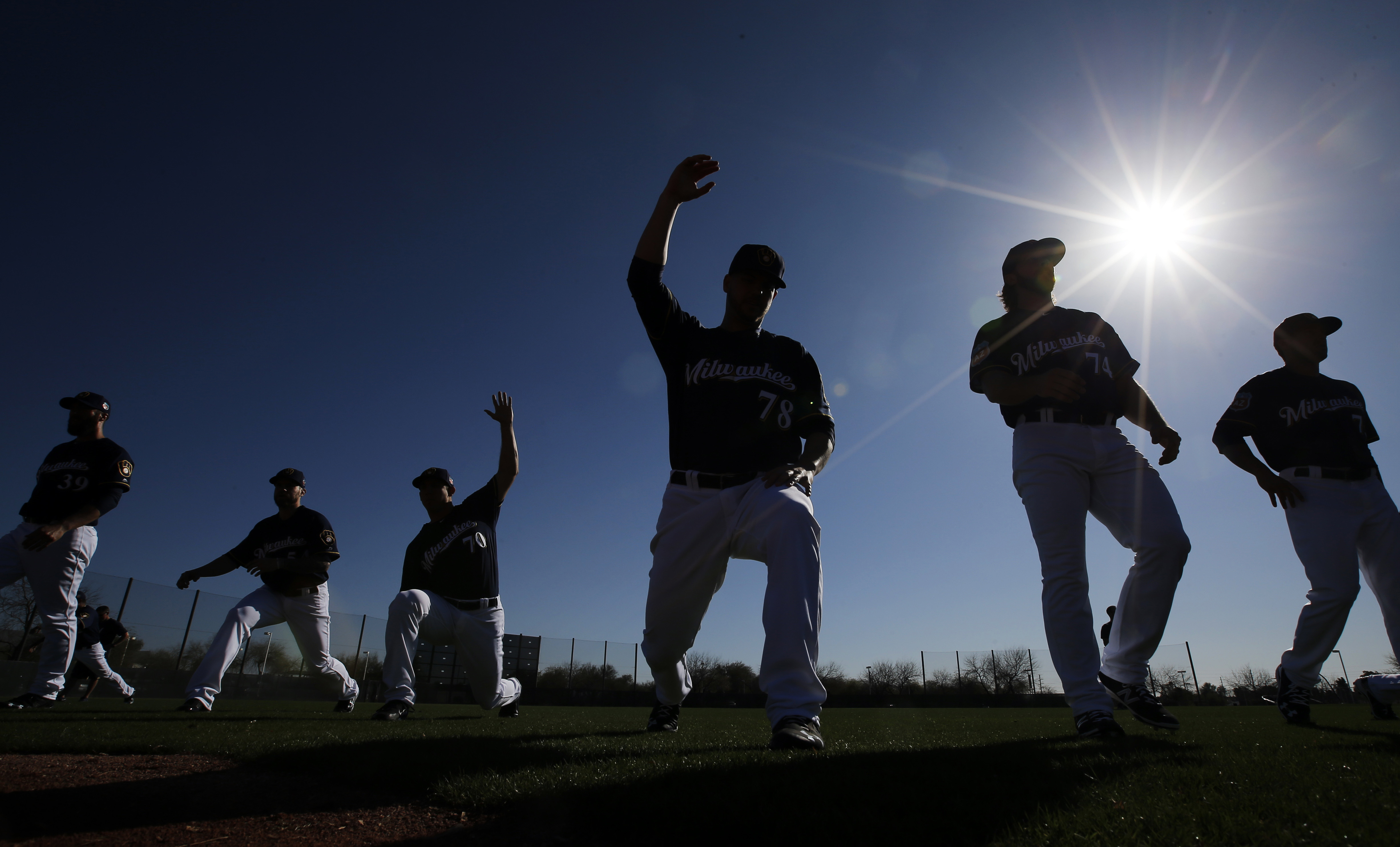 Milwaukee Brewers pitchers and catchers stretch during a spring training baseball workout Sunday, Feb. 21, 2016, in Phoenix. (AP Photo/Morry Gash)
