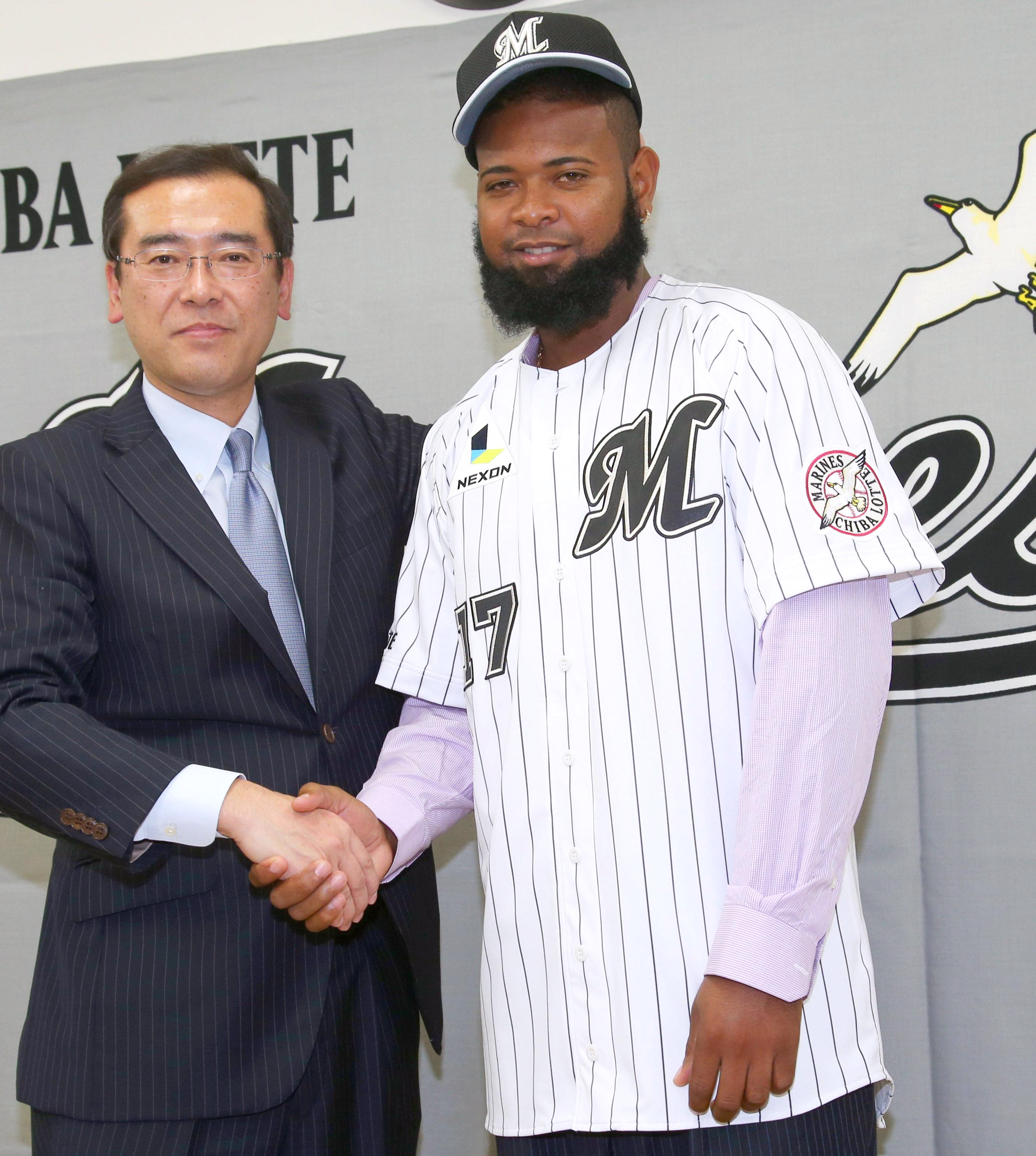 In this Feb. 2, 2016 photo, Yamaico Navarro wearing Lotte Marines' uniform poses with the team's director Shinpei Hayashi for photographers after joining the Japanese professional baseball team in Ishigaki, Okinawa prefecture, southern Japan. Former Major