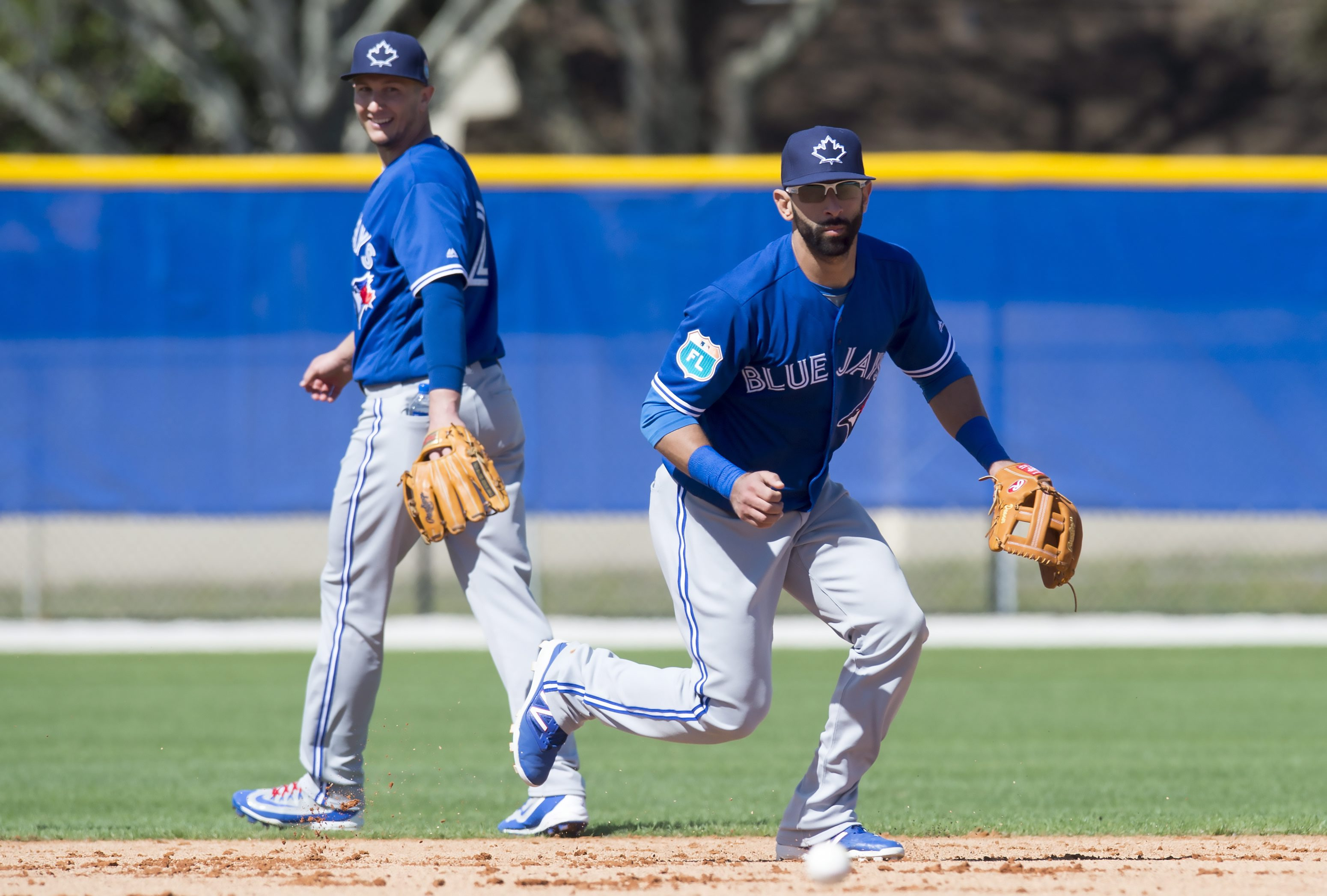 Toronto Blue Jays outfielder Jose Bautista takes ground balls at shortstop as shortstop Troy Tulowitzki, left, smiles and watches during the first official spring training baseball workout in Dunedin, Fla., Monday Feb. 22, 2016. (Frank Gunn/The Canadian P