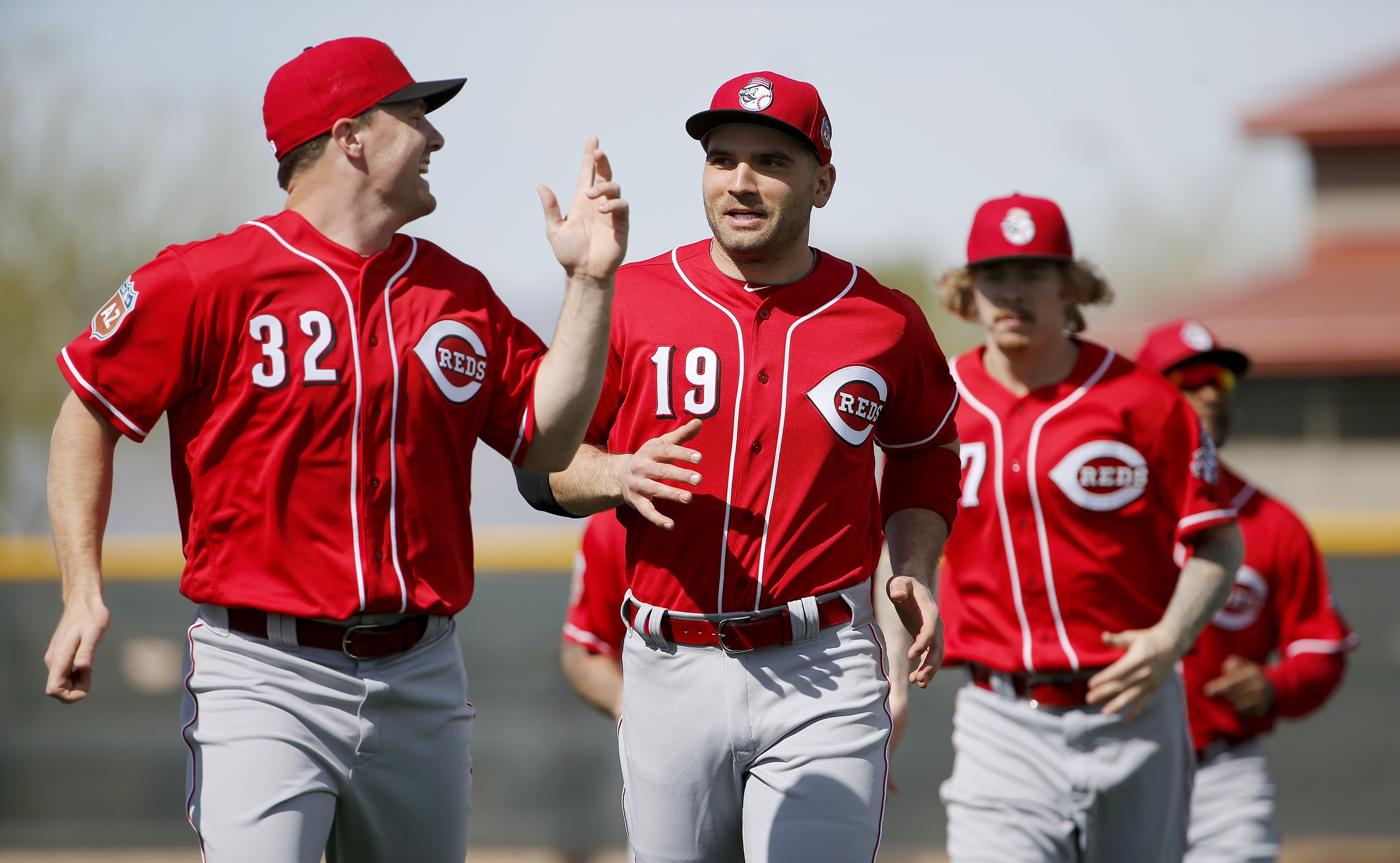 Cincinnati Reds' Joey Votto (19) talks with Jay Bruce (32) as they join teammates in running sprints during a spring training baseball workout Tuesday, Feb. 23, 2016, in Goodyear, Ariz. (AP Photo/Ross D. Franklin)
