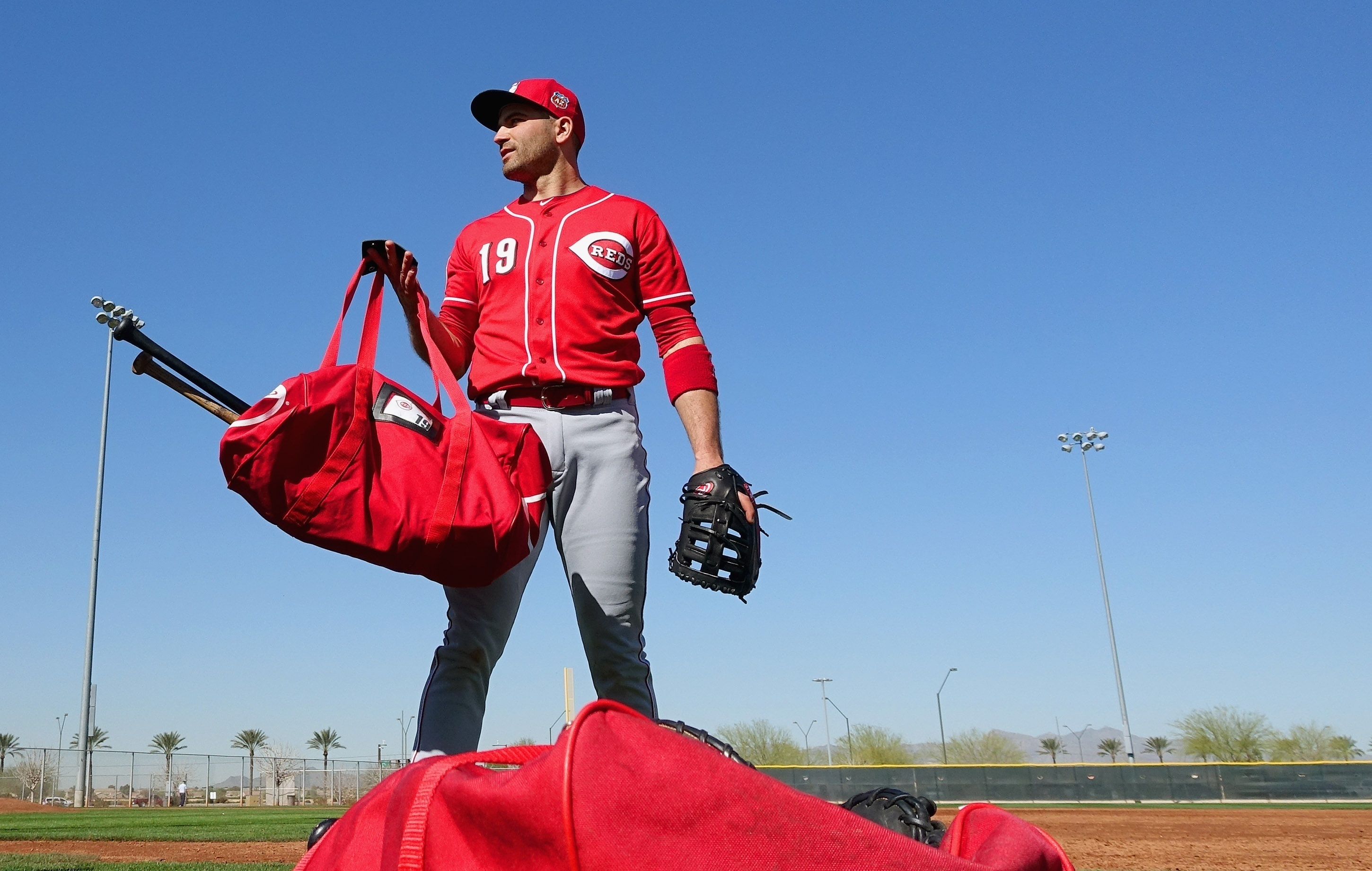 Cincinnati Reds' Joey Votto picks up his equipment bag as he gets ready to move to another practice field during a spring training baseball workout Thursday, Feb. 25, 2016, in Goodyear, Ariz. (AP Photo/Ross D. Franklin)