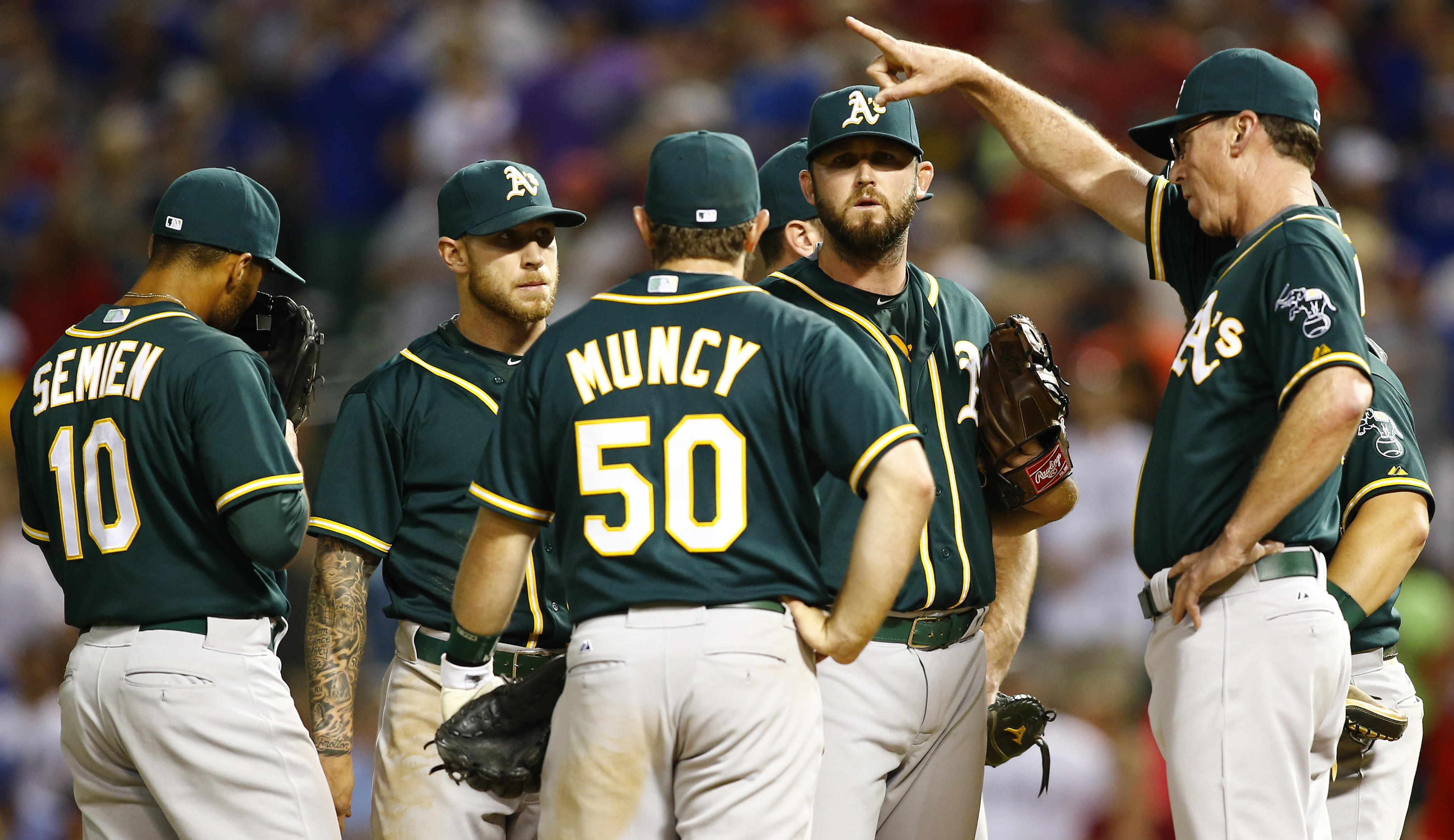 FILE - In this May 2, 2015, file photo, Oakland Athletics manager Bob Melvin signals to the bullpen as pitcher Ryan Cook, second from right, is removed from the lineup against the Texas Rangers in the tenth inning of a baseball game, in Arlington, Texas.