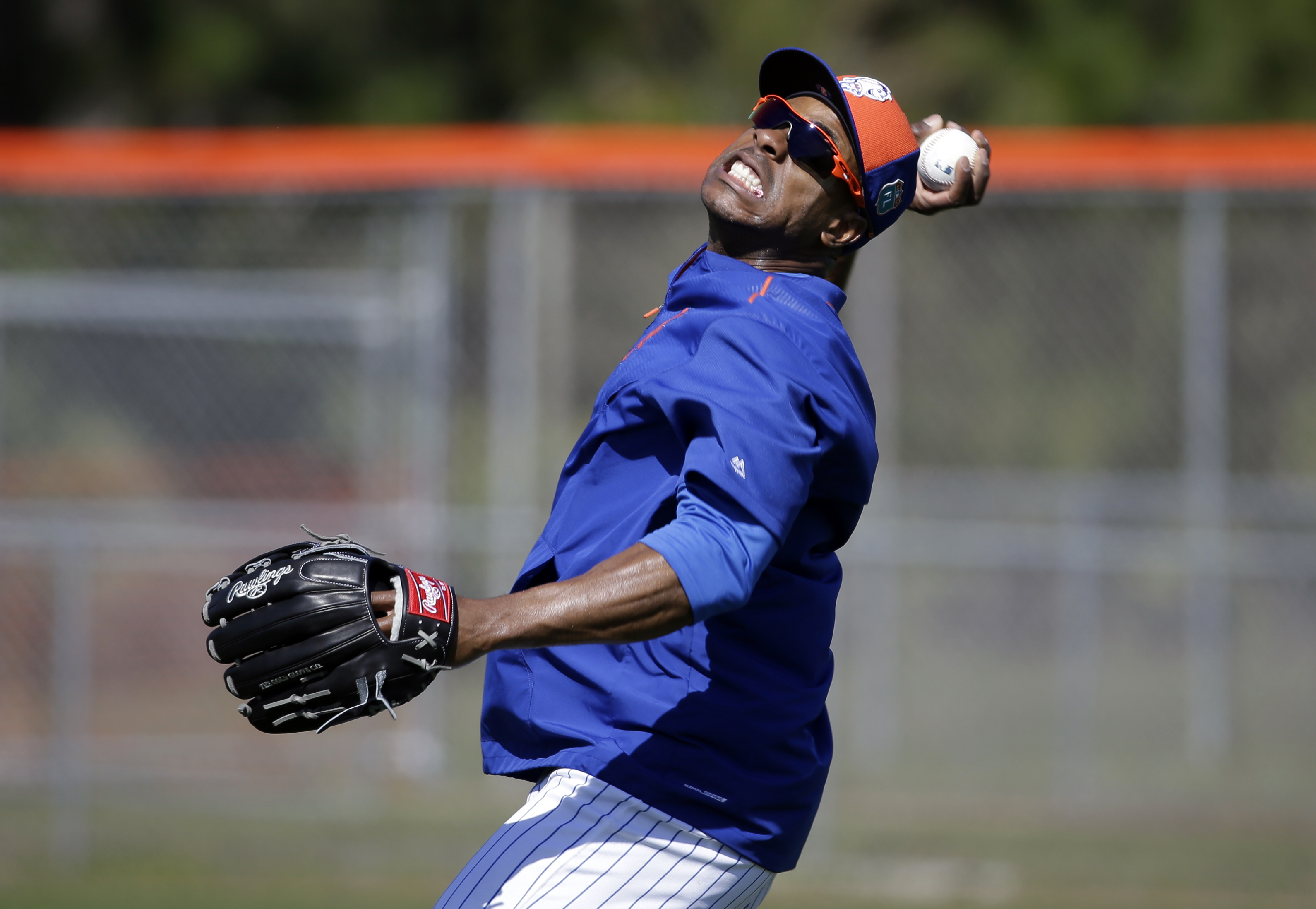 New York Mets' Curtis Granderson jokes as he pretends to heave a ball in from the outfield during spring training baseball practice Friday, Feb. 26, 2016, in Port St. Lucie, Fla. (AP Photo/Jeff Roberson)