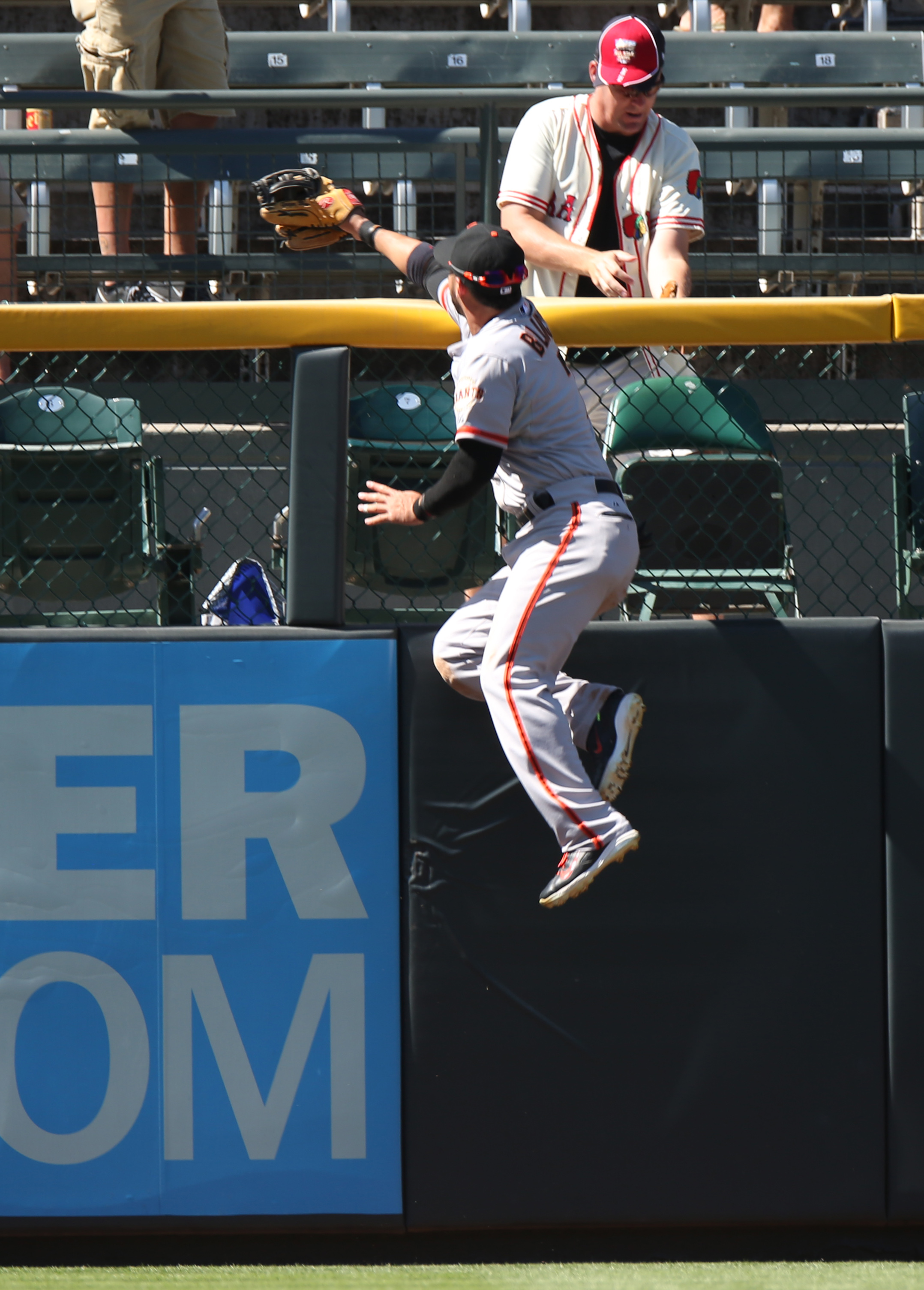 FILE - In this Sept. 3, 2014, file photo, San Francisco Giants left fielder Gregor Blanco climbs the fence in a failed attempt to catch a three-run home run by Colorado Rockies' Nolan Arenado in the fifth inning of the Rockies' 9-2 victory in a baseball g