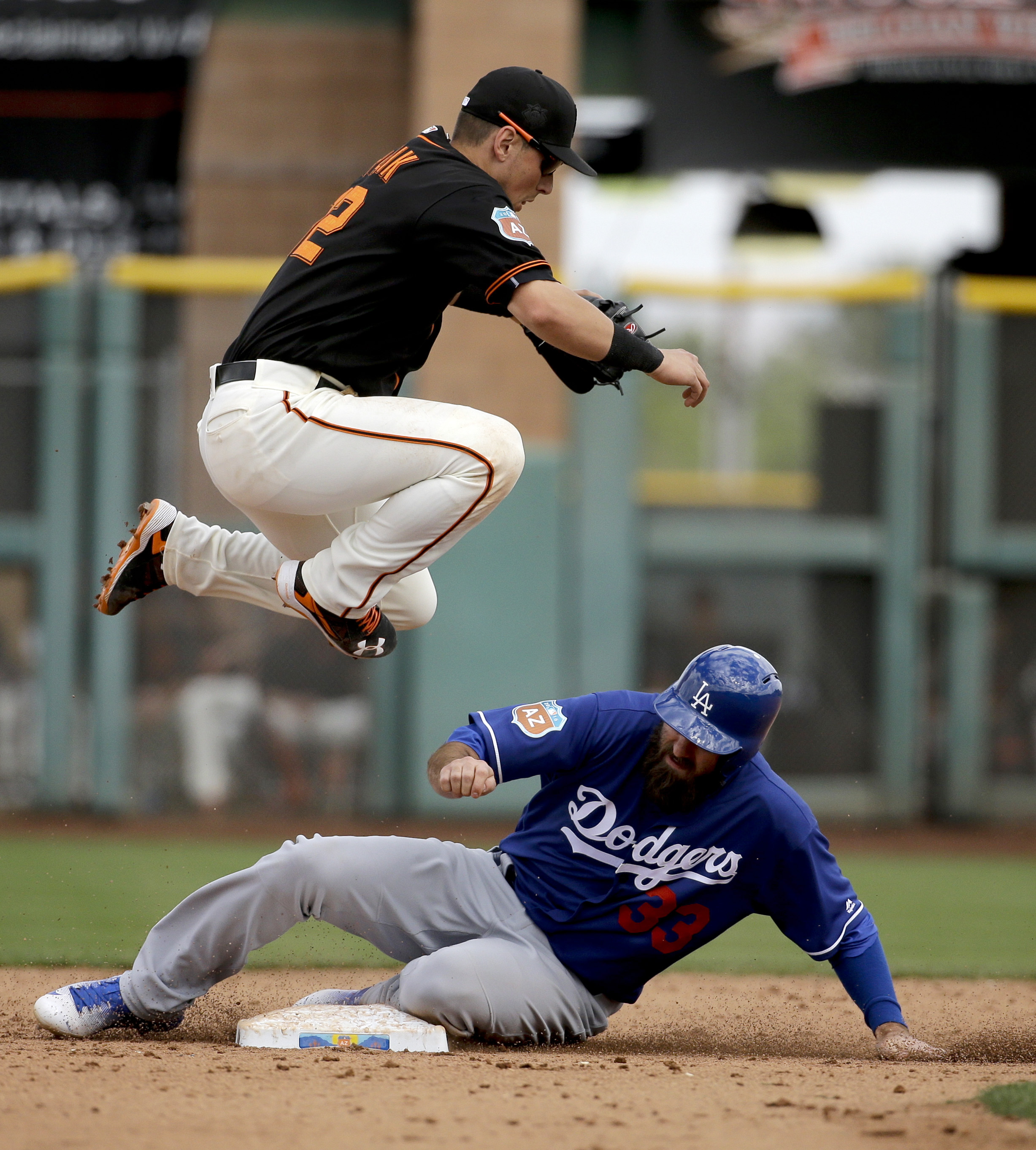 San Francisco Giants second baseman Joe Panik, top, forces Los Angeles Dodgers' Scott Van Slyke, bottom, out at second after A.J. Ellis hit into a double play during sixth inning of a spring baseball game in Scottsdale, Ariz., Sunday, March 6, 2016. (AP P