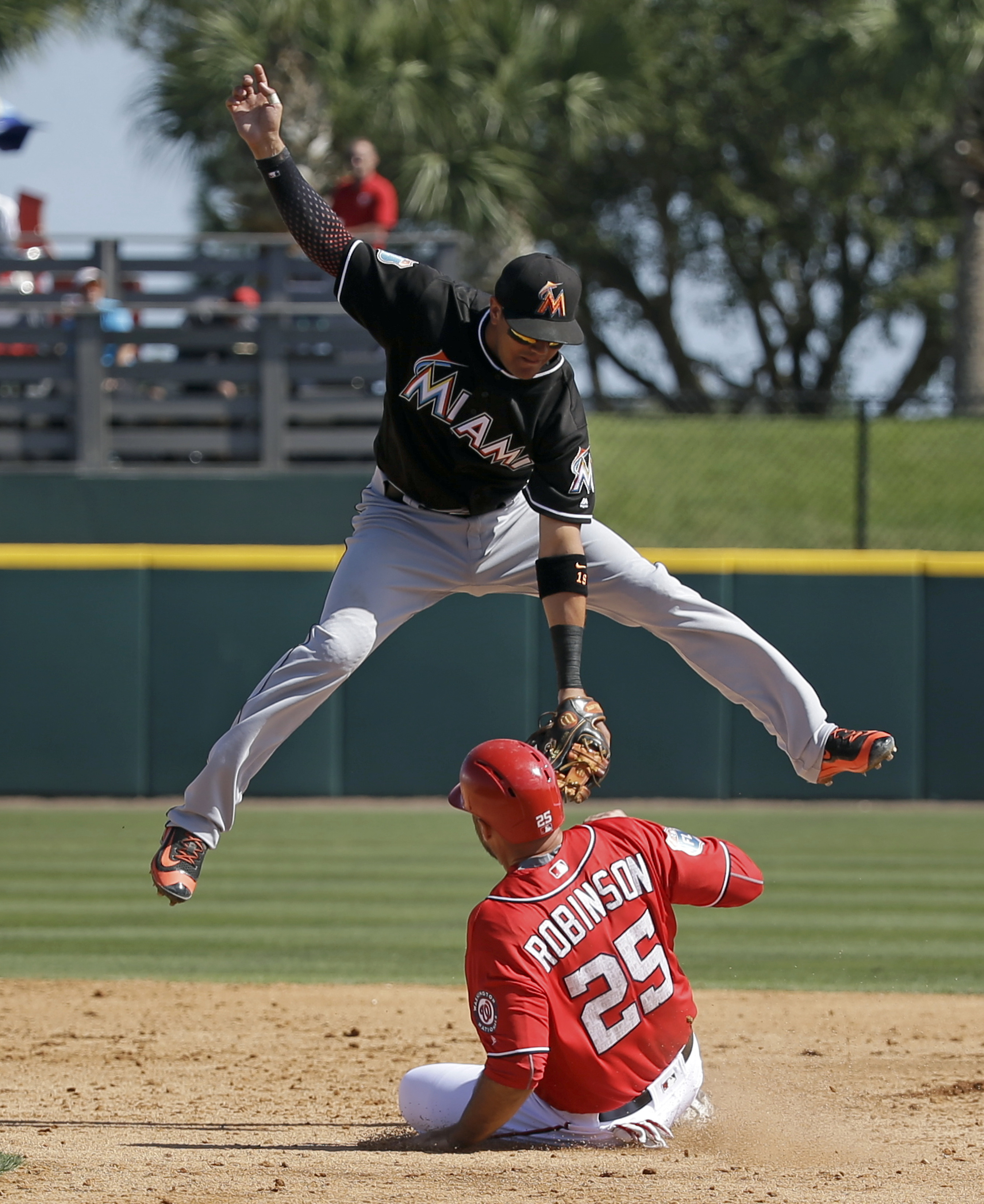 Washington Nationals' Clint Robinson (25) steals second base in the fourth inning as Miami Marlins shortstop Miguel Rojas cannot make the tag due to a high throw from the catcher in a spring training baseball game, Monday, March 7, 2016, in Viera, Fla. (A