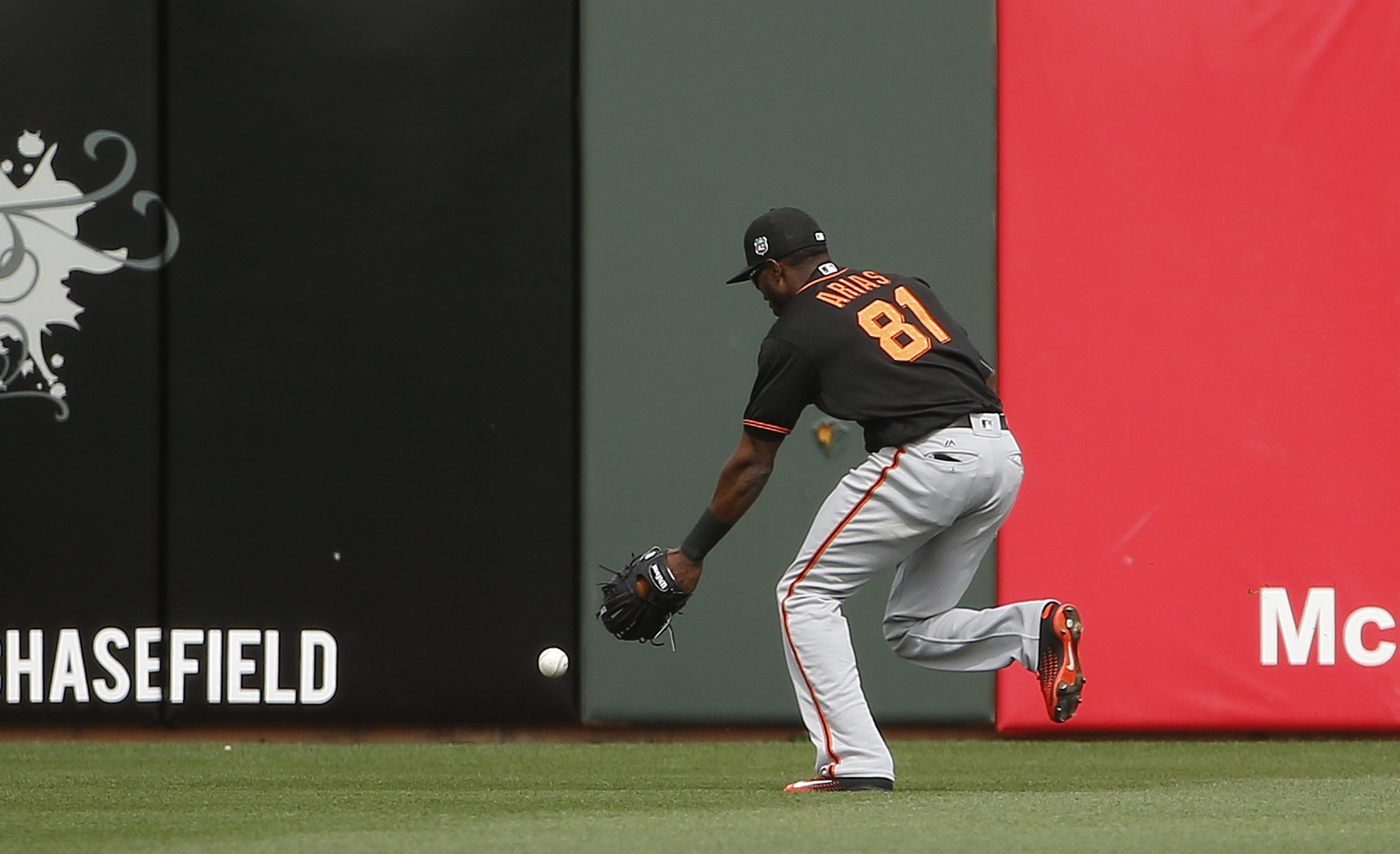 San Francisco Giants' Junior Arias drops a fly ball hit by Texas Rangers' Pedro Ciriaco during the second inning of a spring training baseball game Monday, March 7, 2016, in Surprise, Ariz. Rangers' Ciriaco reached second base on the error. (AP Photo/Ross
