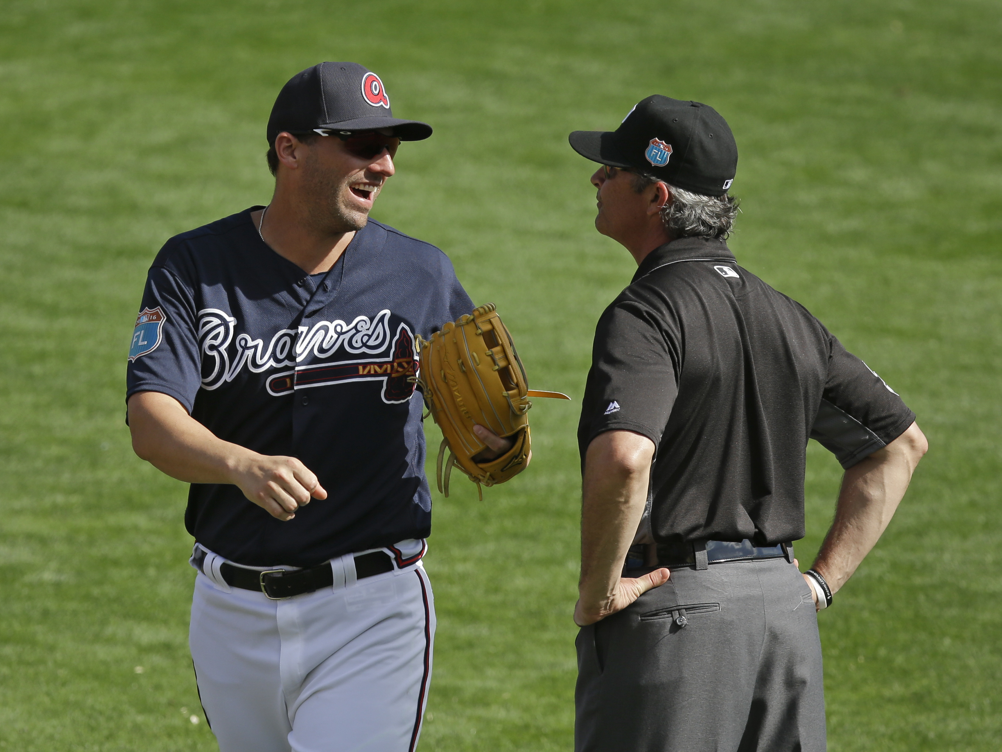 Atlanta Braves Jeff Francoeur chats with umpire Paul Nauert between innings in a spring training baseball game against the New York Mets, Tuesday, March 8, 2016, in Kissimmee, Fla. (AP Photo/John Raoux)