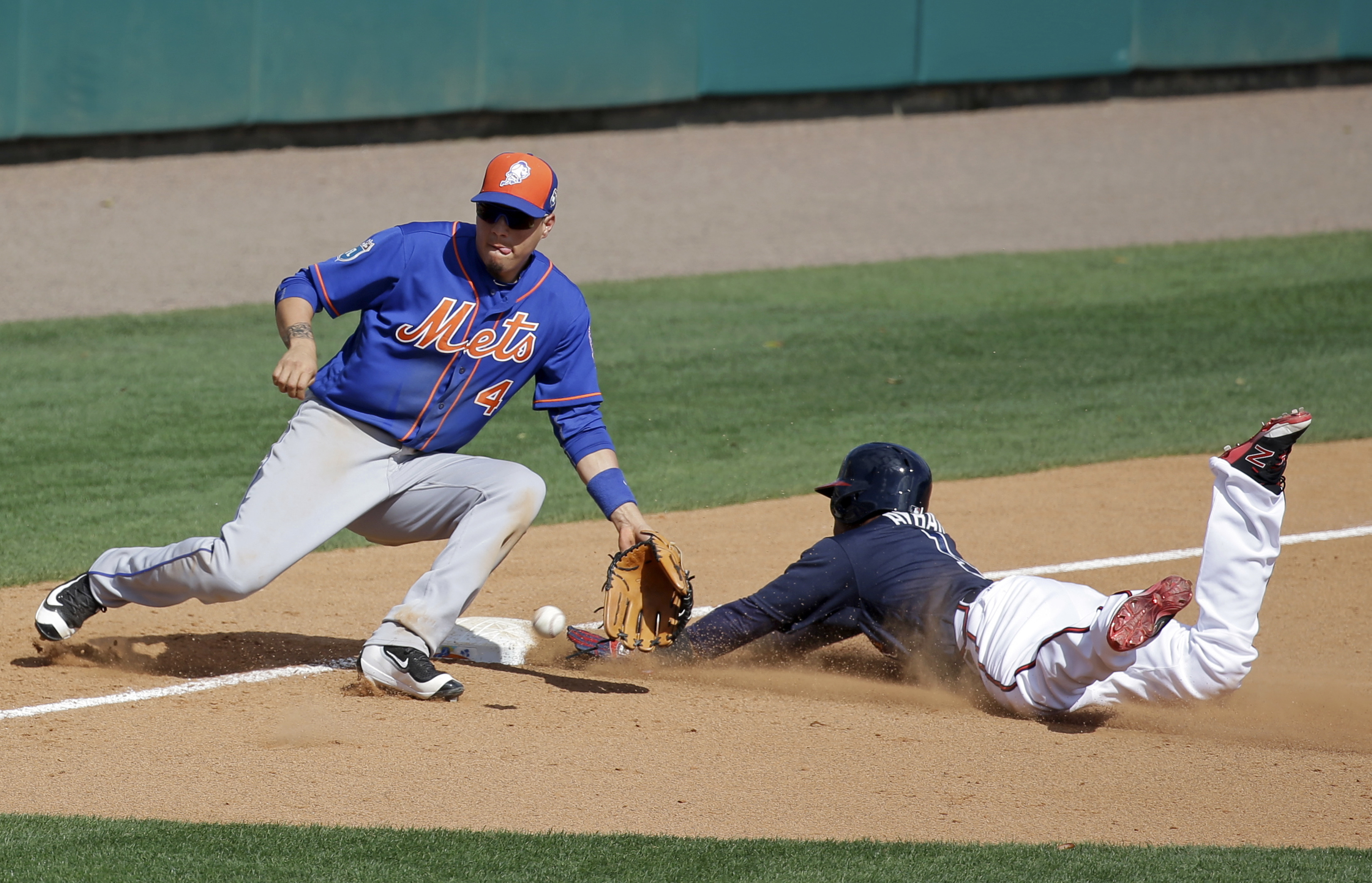 Atlanta Braves' Erick Aybar, right, slides into third base as New York Mets shortstop Wilmer Flores waits for the ball to make the tag during the fifth inning of a spring training baseball game, Tuesday, March 8, 2016, in Kissimmee, Fla. (AP Photo/John Ra